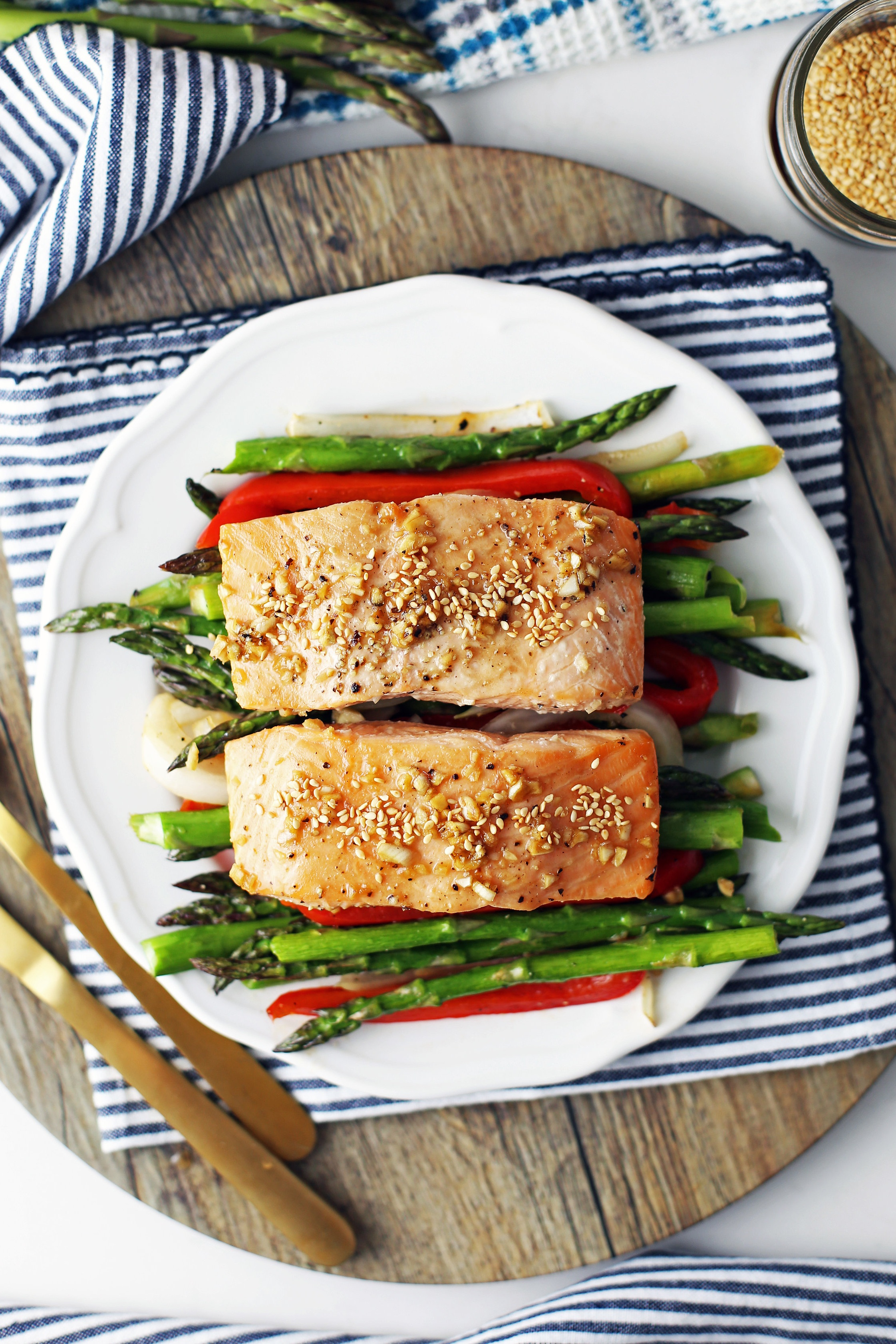 Overhead view of two baked salmon fillets on a bed of roasted asparagus, bell pepper, and onions on a white plate.