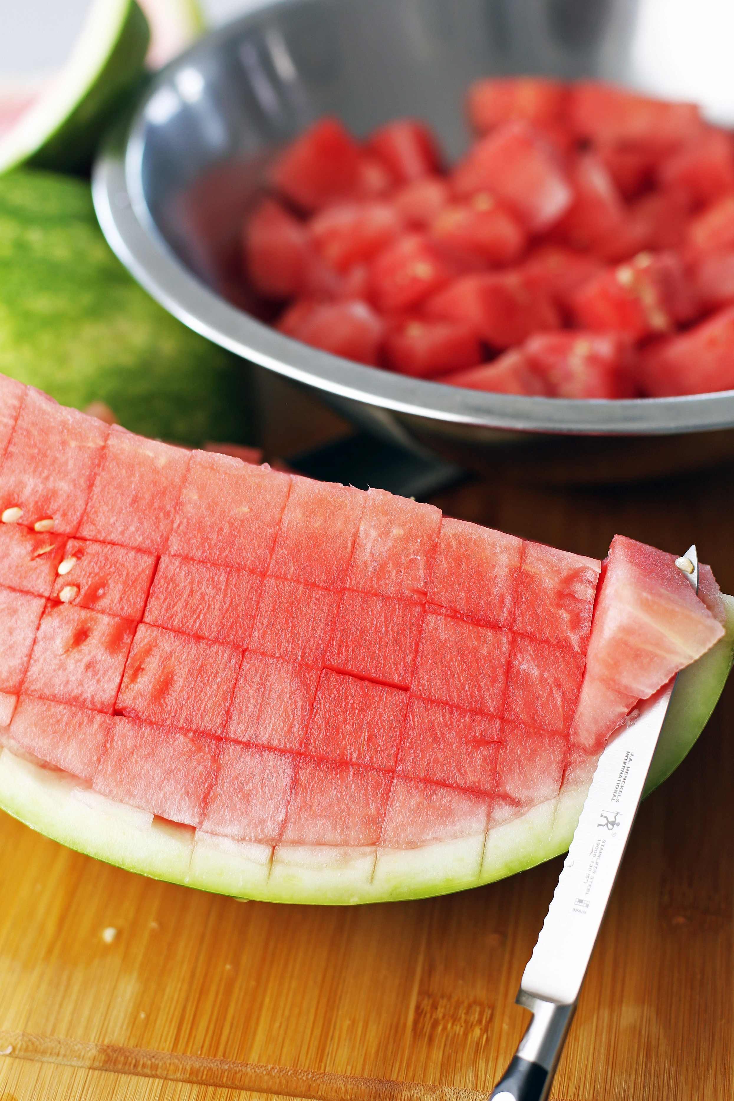A quarter seedless watermelon with knife cuts in it with a serrated knife cutting into it.
