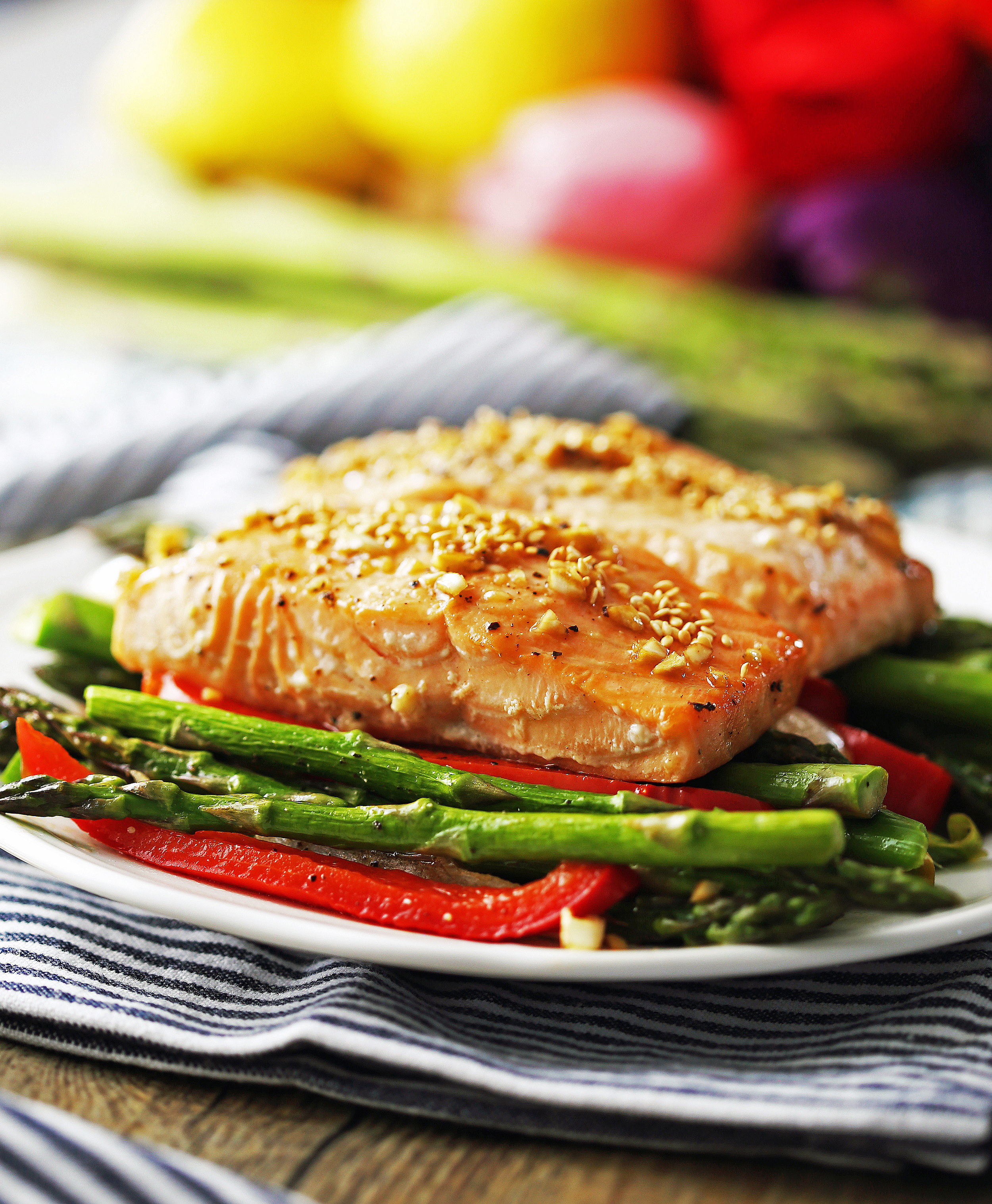 Two baked honey garlic salmon fillets with asparagus and bell pepper on white plate.