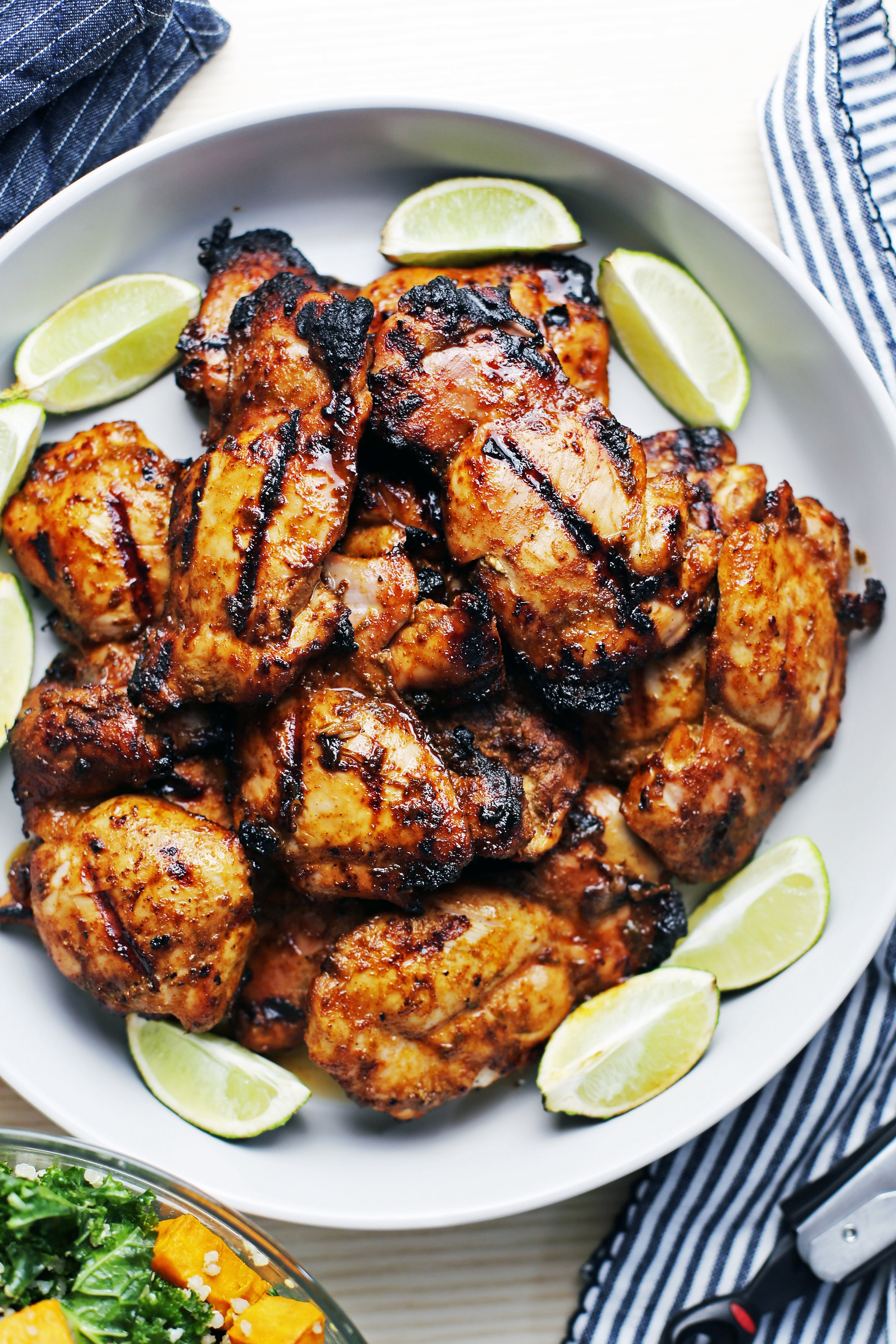 Twelve grilled chili lime chicken thighs on a large grey platter surrounded by lime wedges.