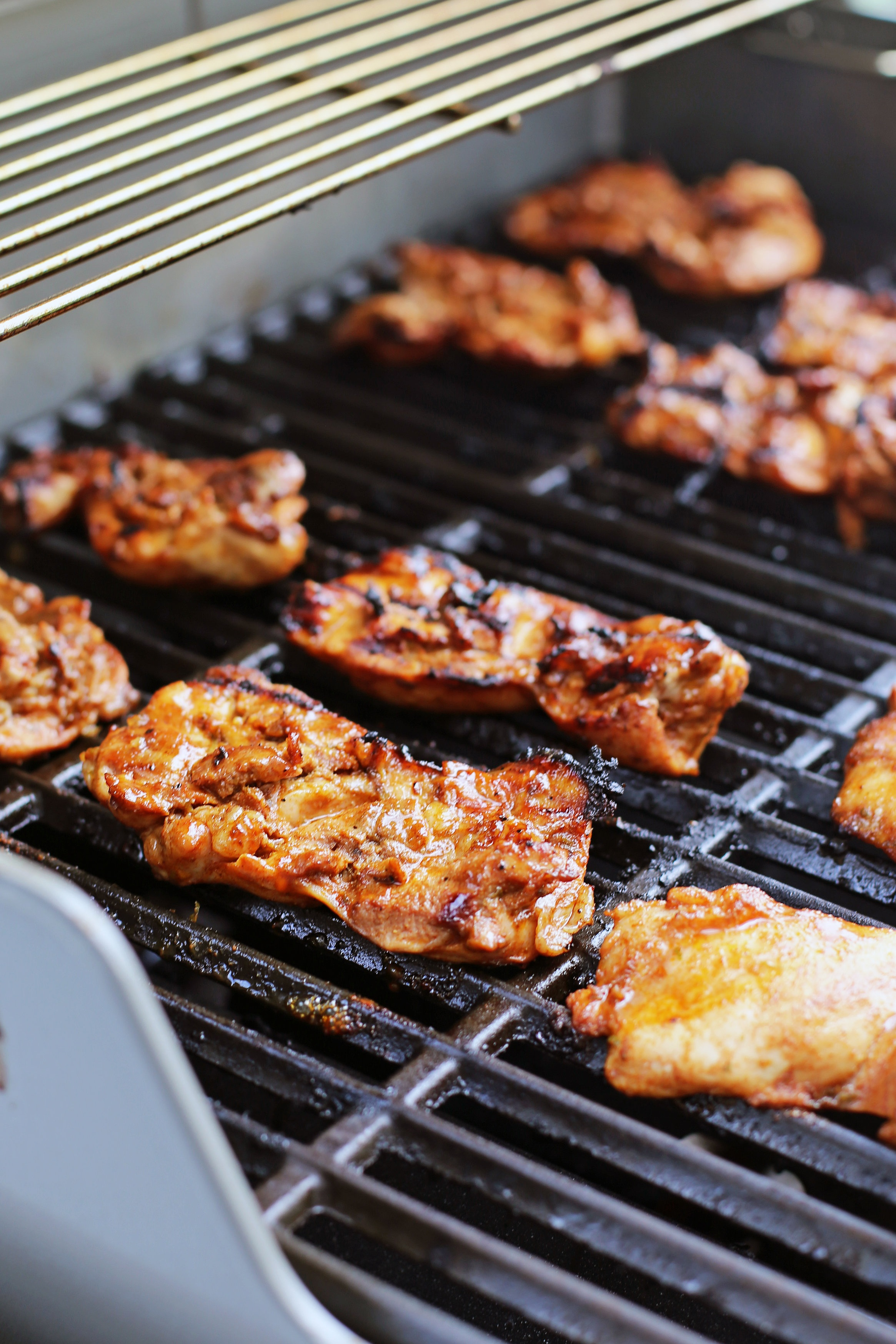 Chili lime chicken thighs cooking on a hot barbecue grill.