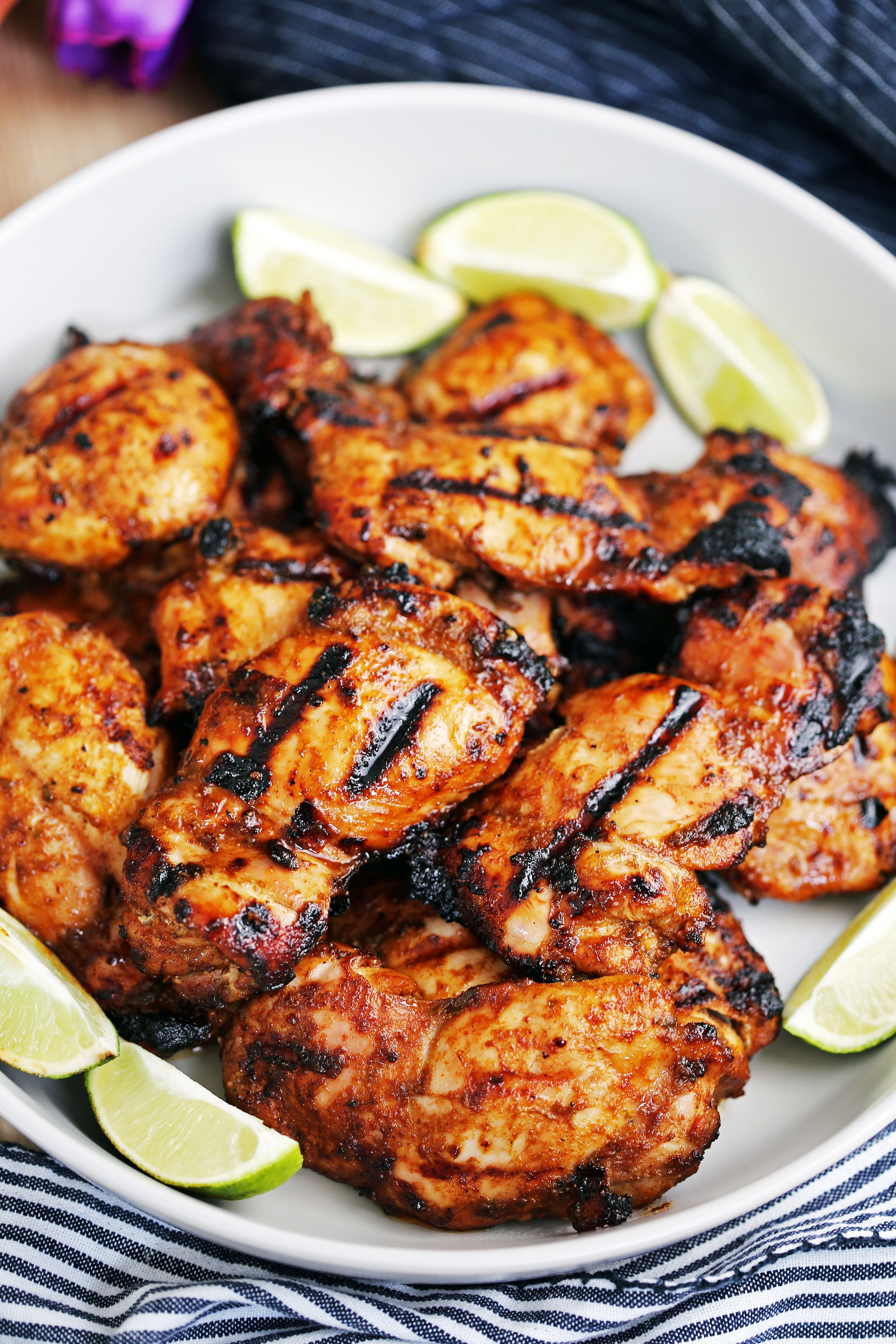 A dozen hot grilled chili lime chicken thighs surrounded by lime wedges on a large grey platter.