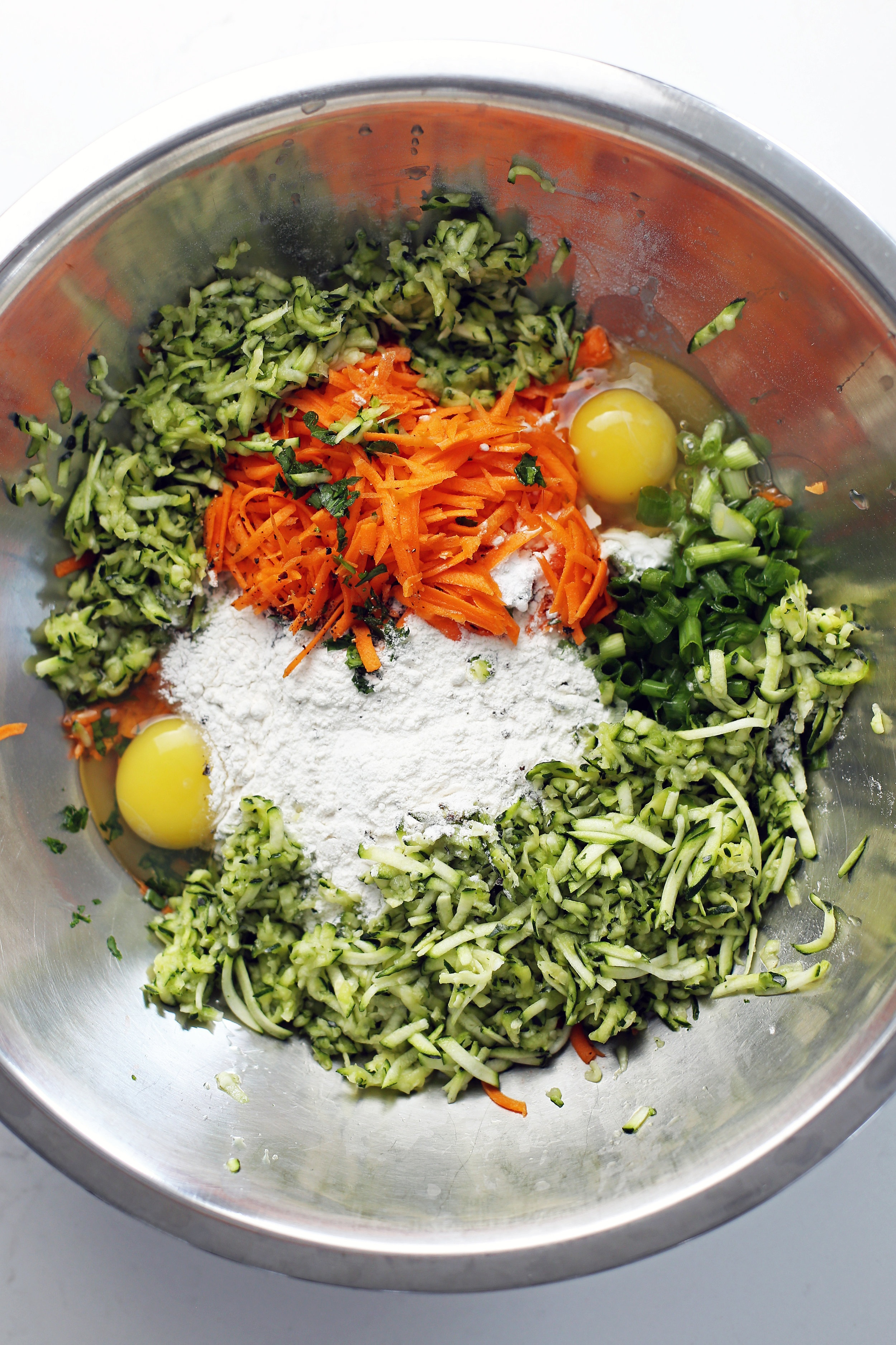 Shredded zucchini, shredded carrots, green onion, parsley, eggs, flour, baking powder, and cracked black pepper in a large stainless steel bowl.
