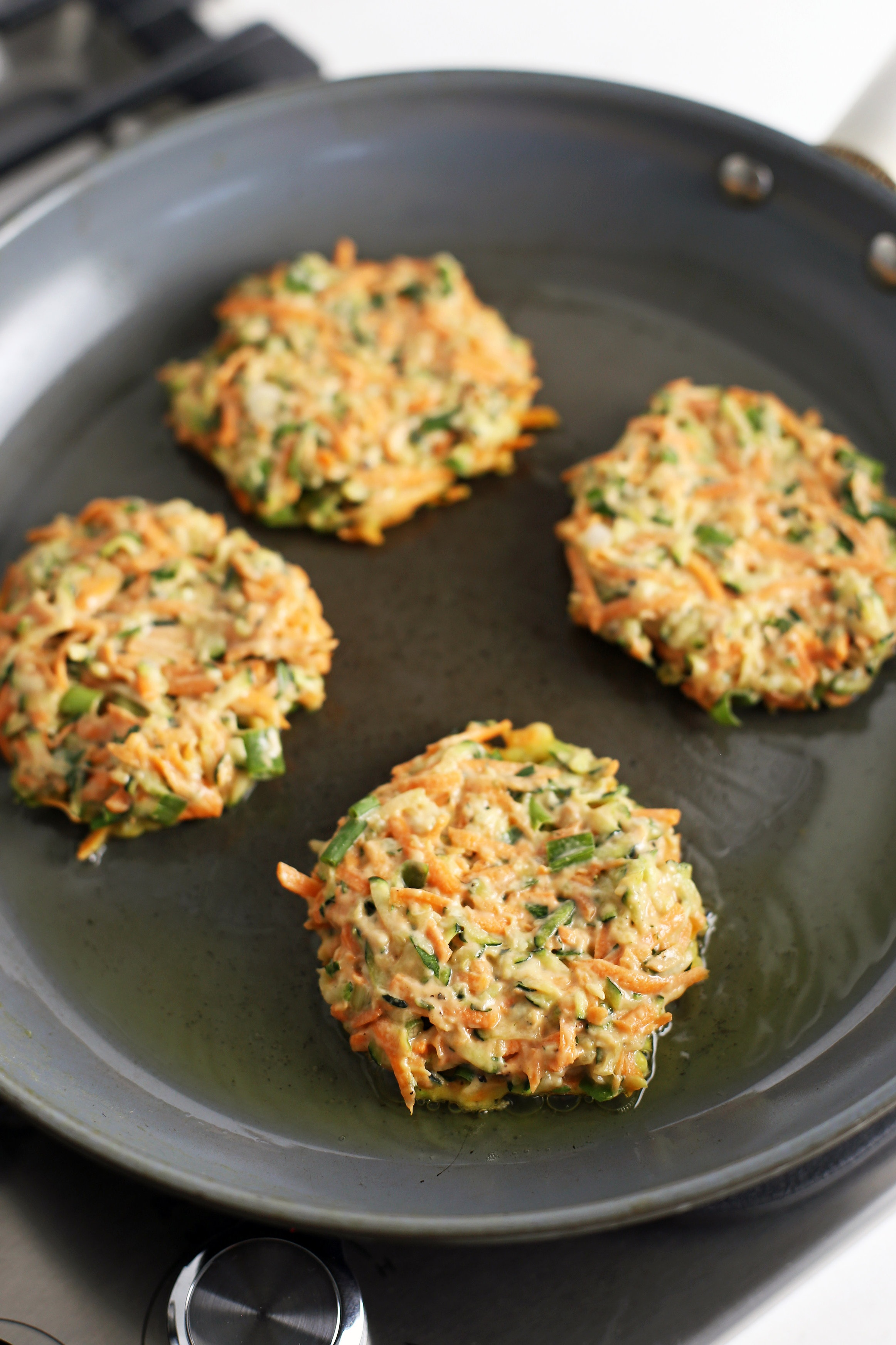 Four zucchini carrot pancakes frying in a small amount of olive oil in a large frying pan.