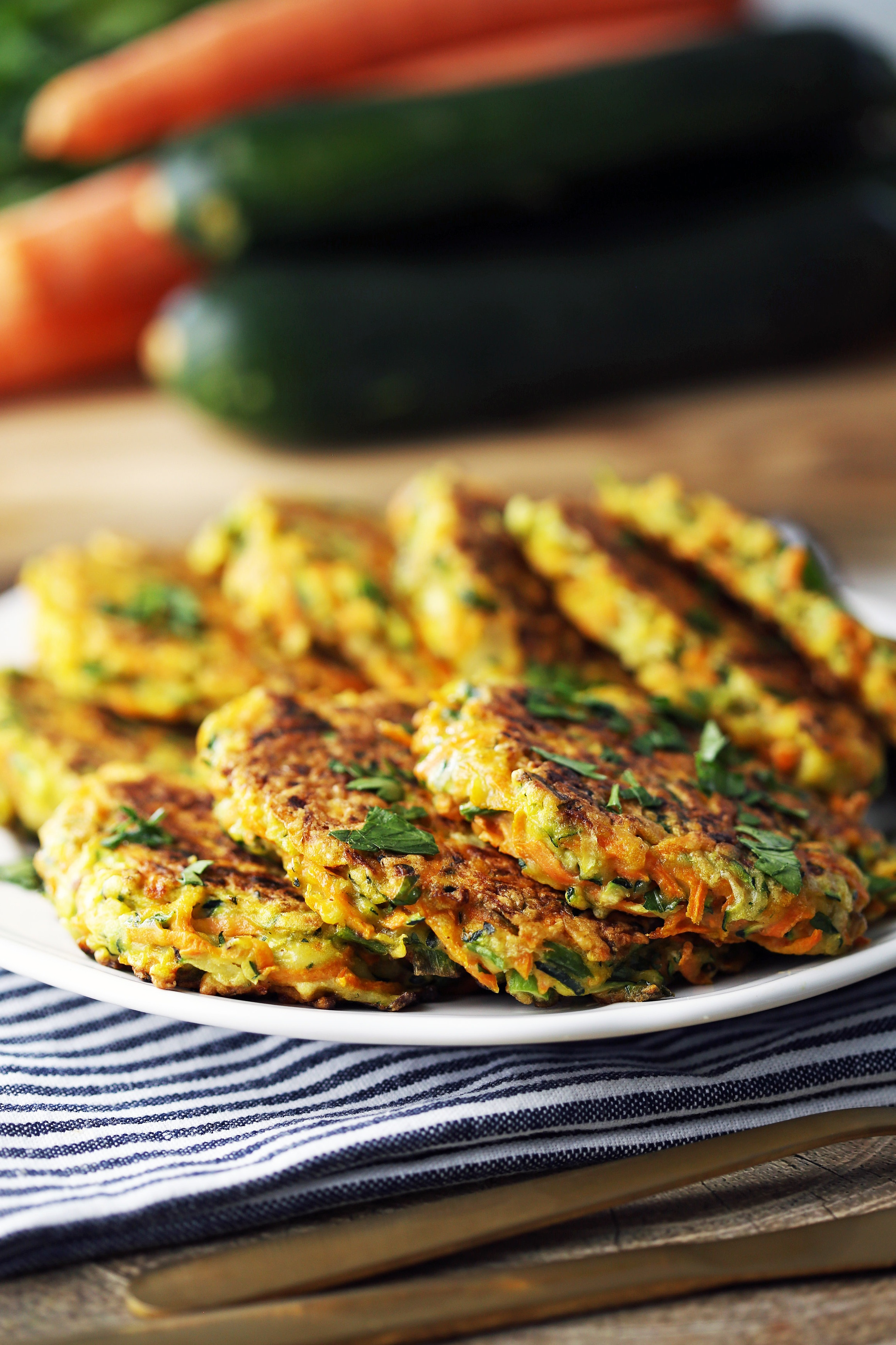 Eight zucchini carrot pancakes topped with fresh parsley on a white plate.