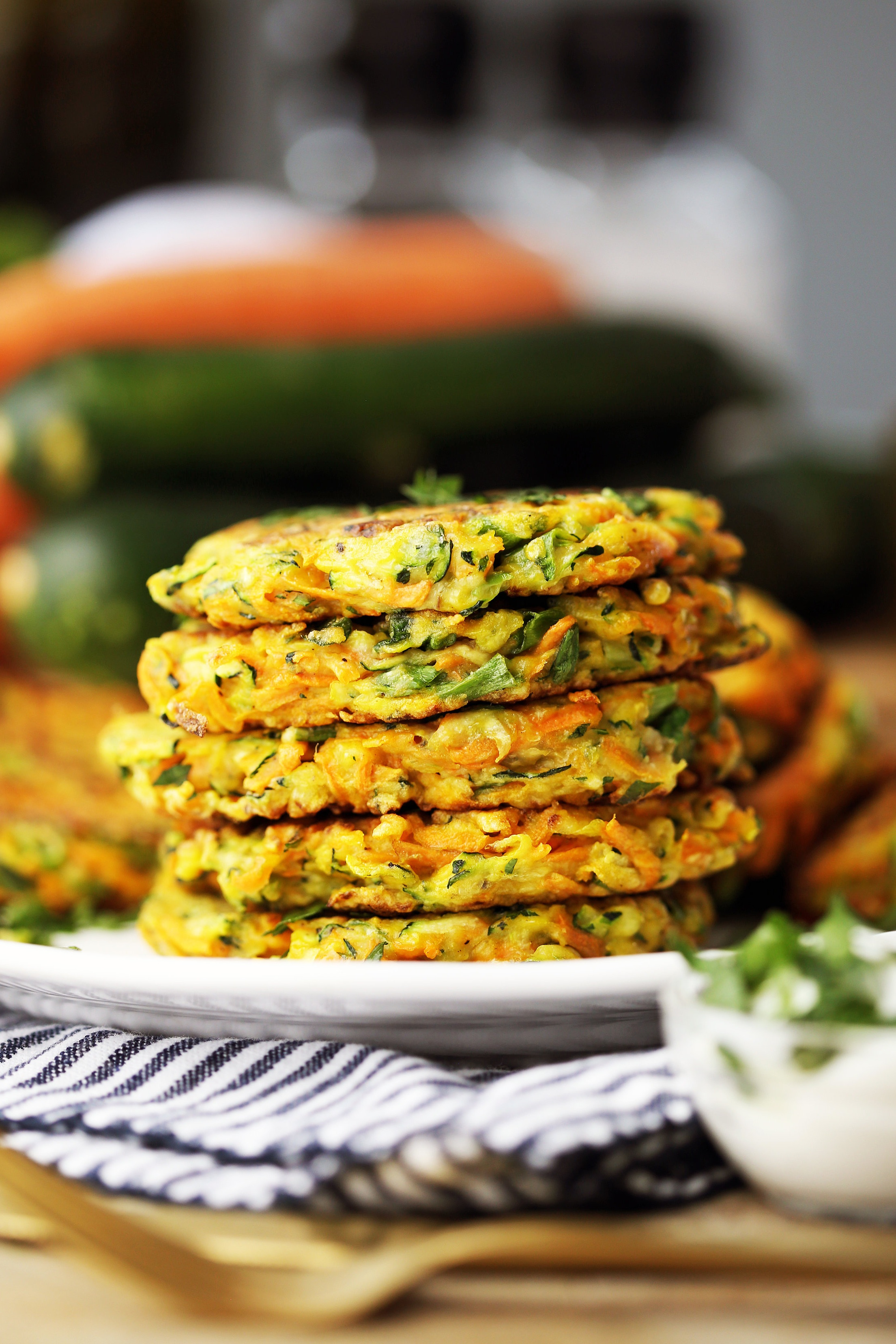 Five zucchini carrot pancakes stacked on a white plate with plain Greek yogurt in a small glass bowl on the side.