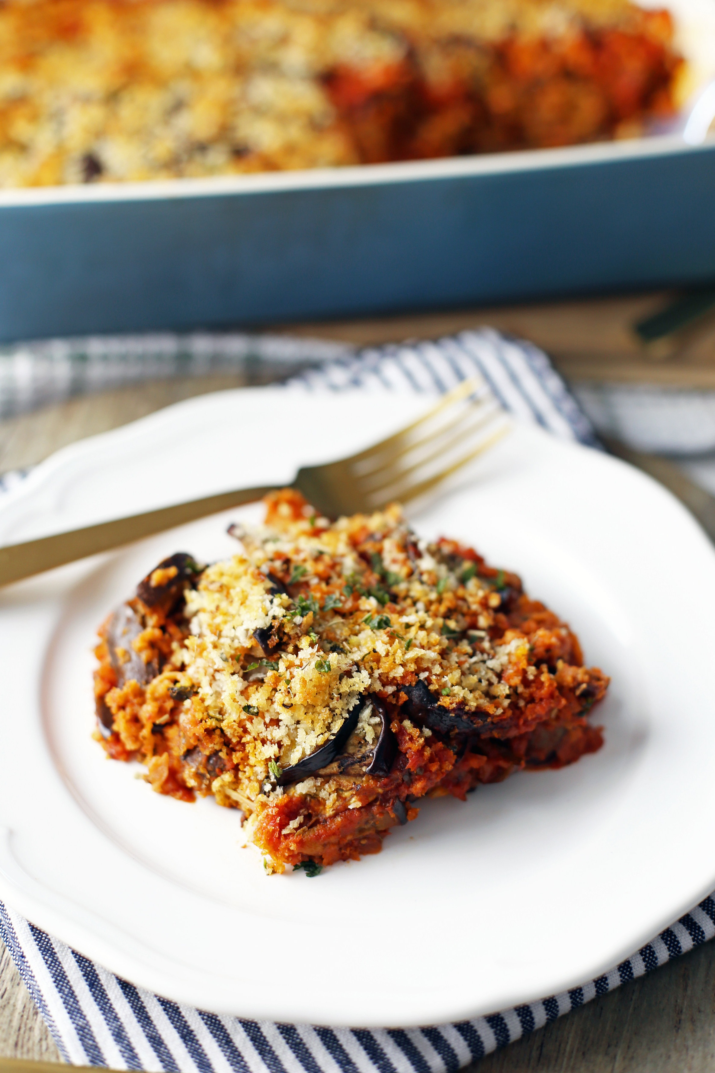 A piece of cheesy layered Baked Eggplant Parmesan on a white plate with a gold fork.