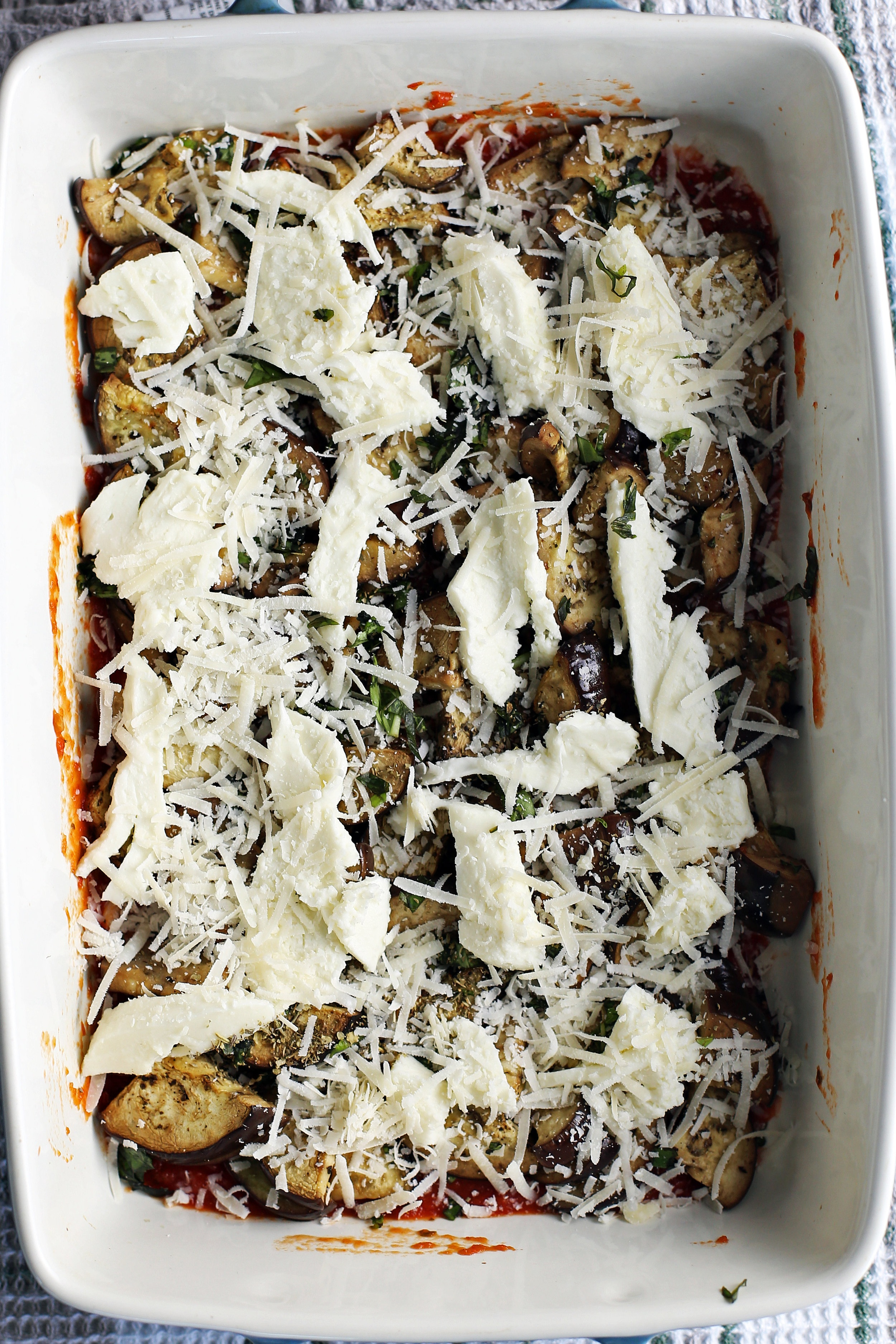 A large casserole dish containing layers of marinara sauce, sliced eggplant, herbs, and cheeses.