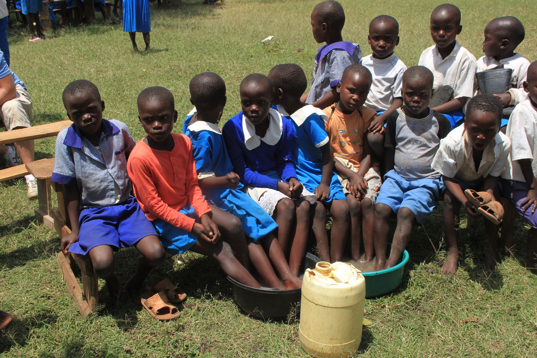 Schoolchildren bathing feet in disinfectant to remove Jiggers