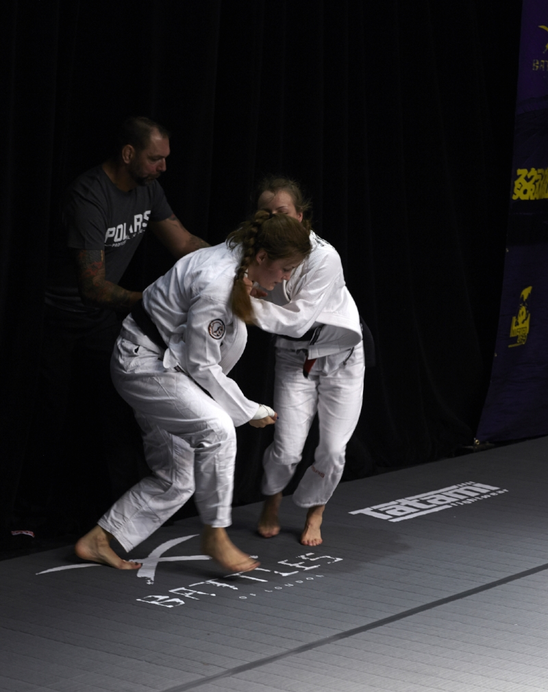 The two top-flight women are ushered back to the centre of the mat. Photo by Andrew Jackson.