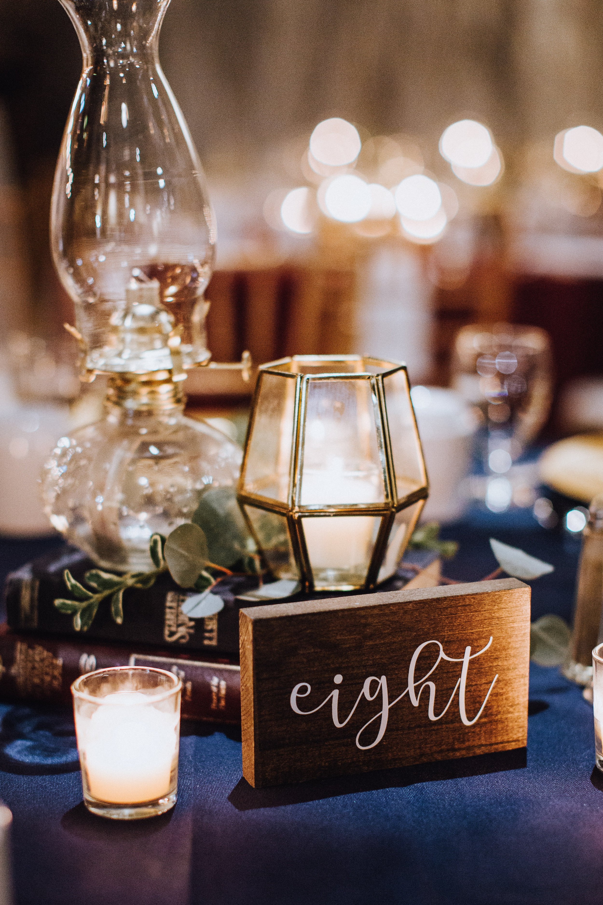 Vintage style oil lamps  Gold and glass candle holders  Vintage assorted colours and sizes books  Photo by  Jenna Rachelle Photography