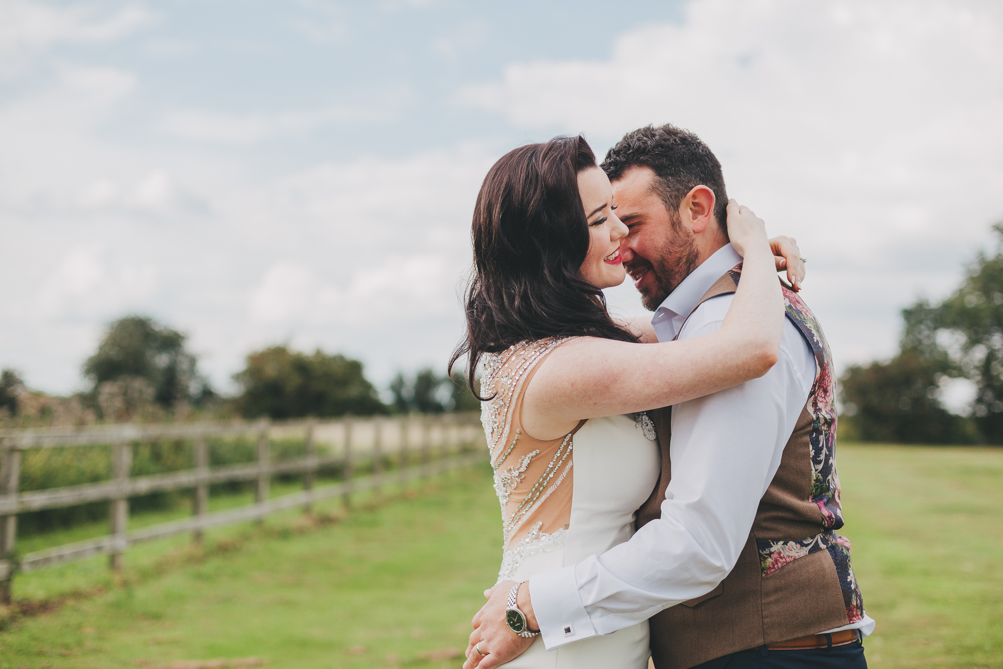 Bride and groom hugging at sunset in a field at Coltsfoot Country Retreat.
