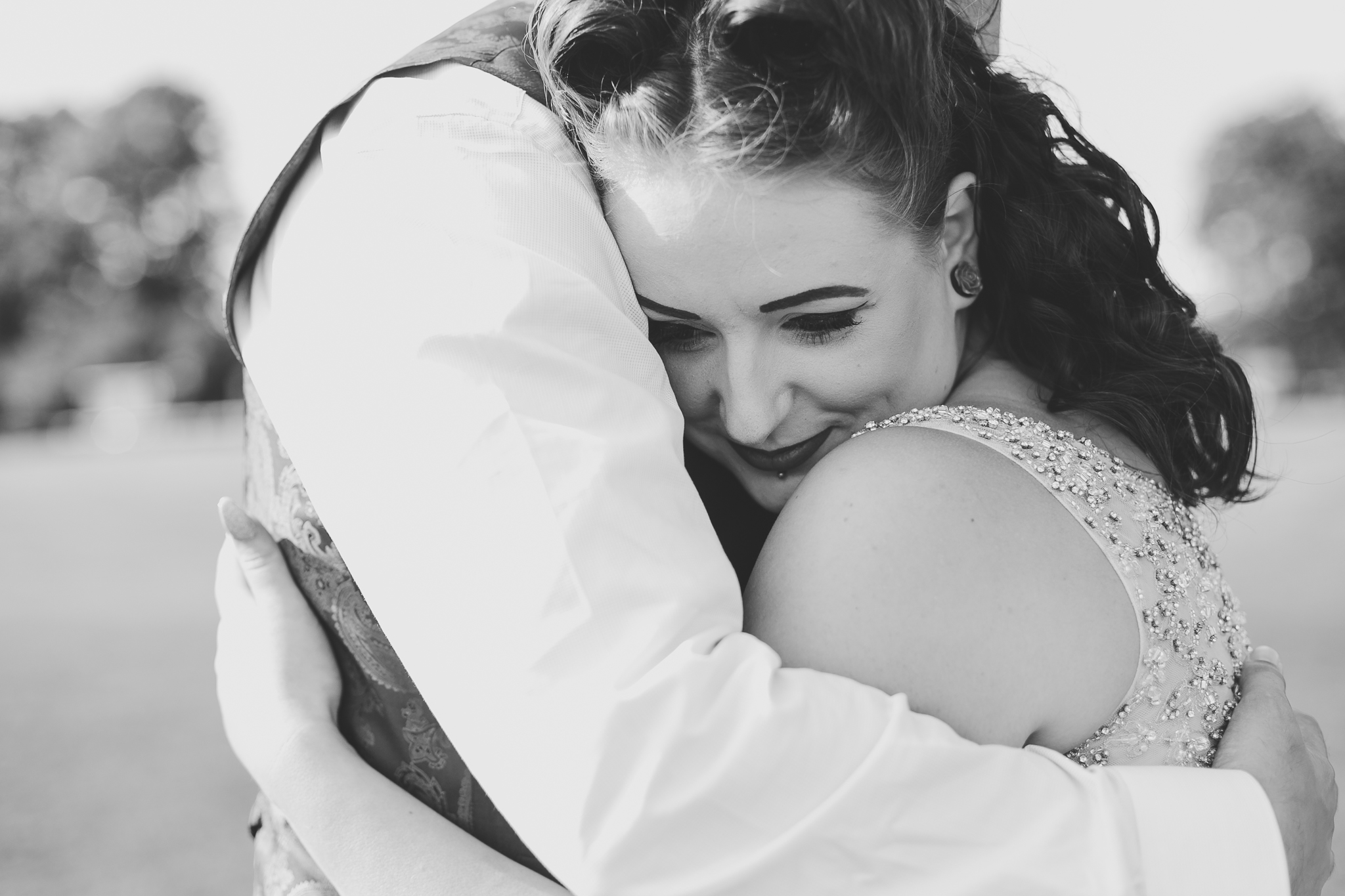 Black and white image of bride hugging groom and smiling