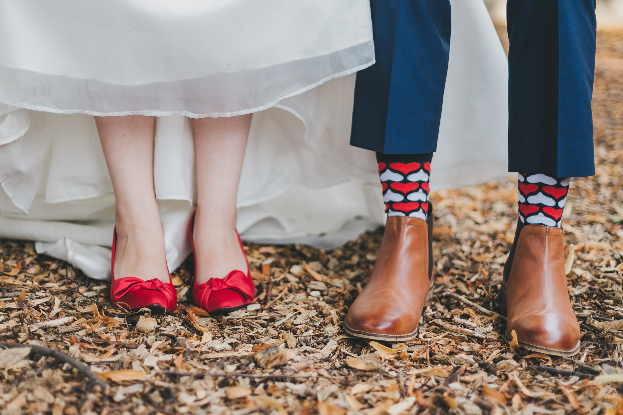 Bride and grooms legs showing red shoes and red heart print socks