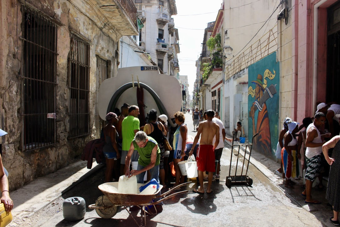 Locals collecting water rations outside of El Cafe in Havana