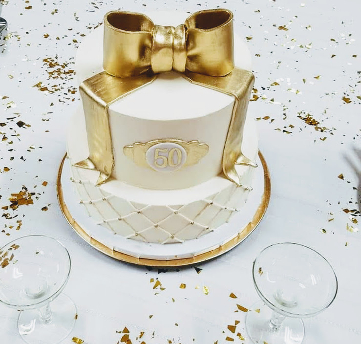 Celebrate the milestones with a cake like this classic white and gold cake made for a 50th Anniversary.