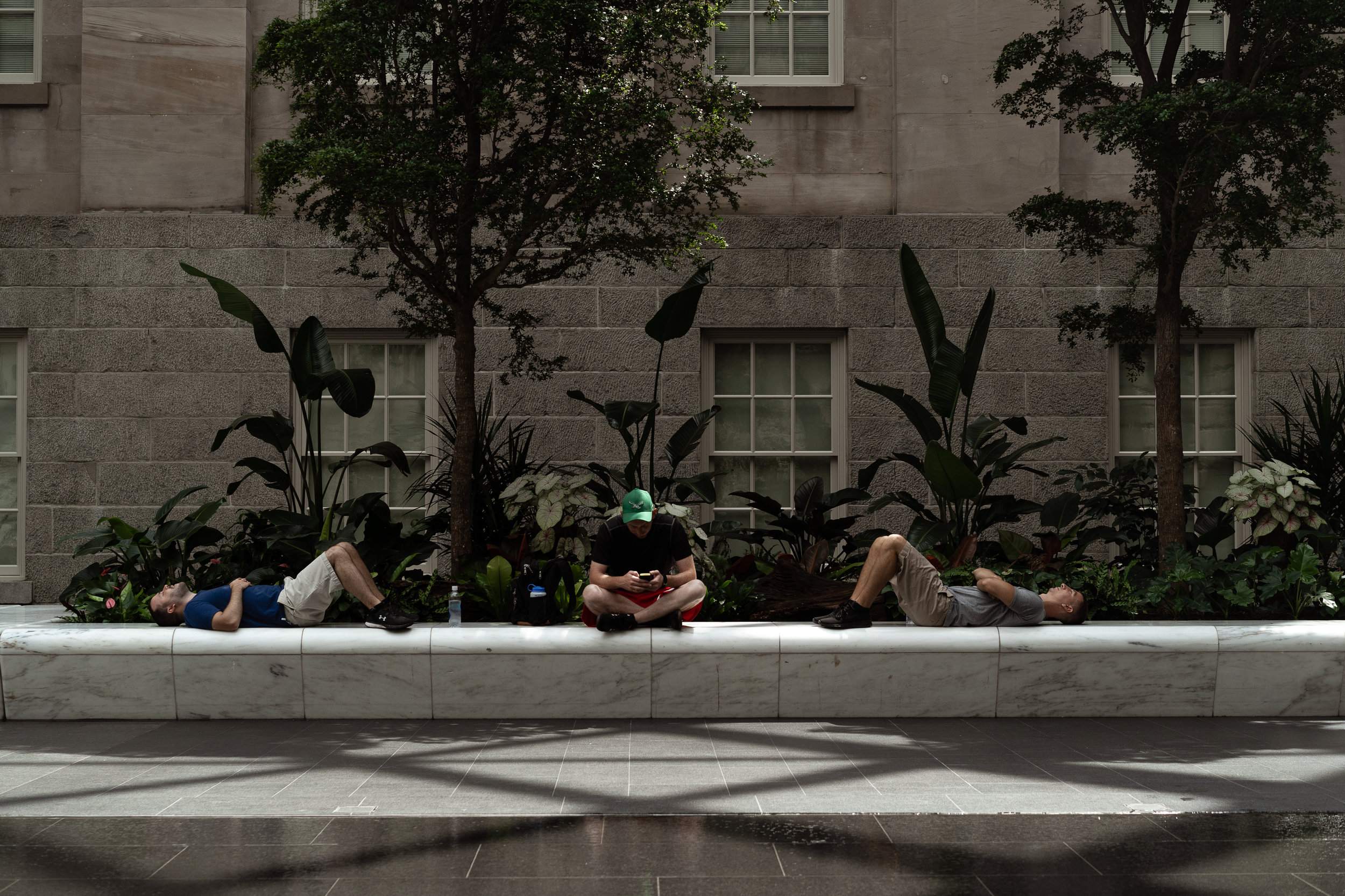 two and a half men taking a moment. - Kogod Courtyard in the National Portrait Gallery.