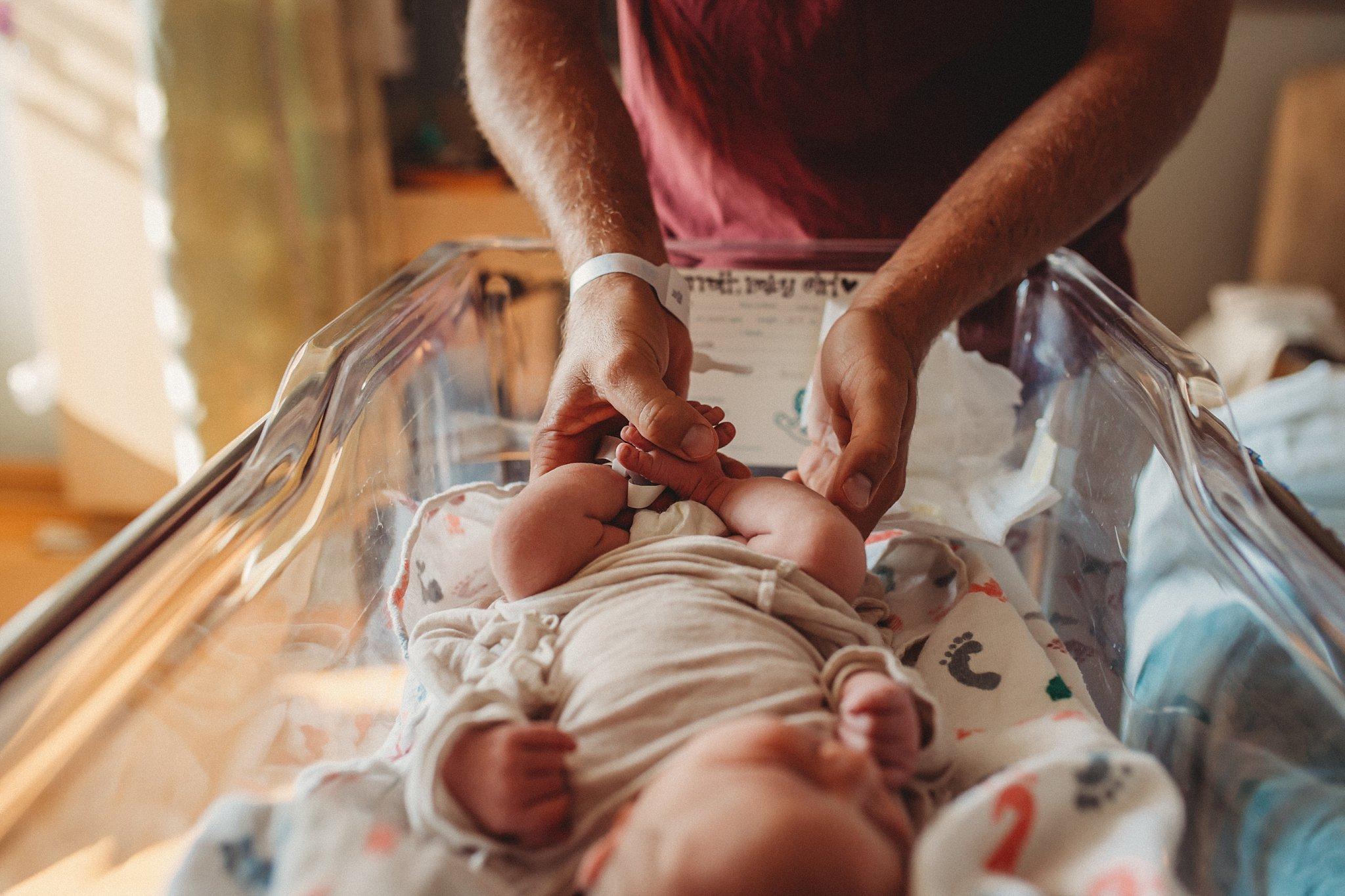 Becci Ravera Photography Family Newborn Photographer dad changing newborn diaper