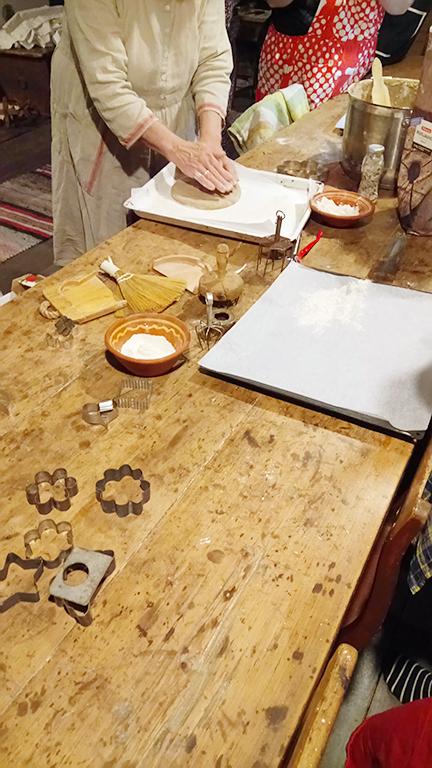 Riitta näyttää meille, kuinka taikinaa muotoillaan. Riitta shows us how the dough is shaped.