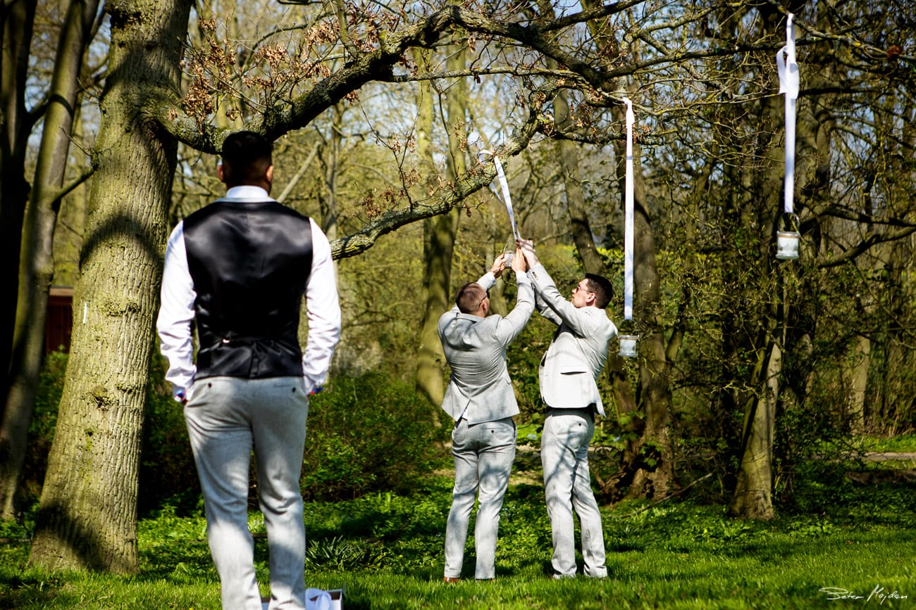 Groomsmen hanging lanterns outside
