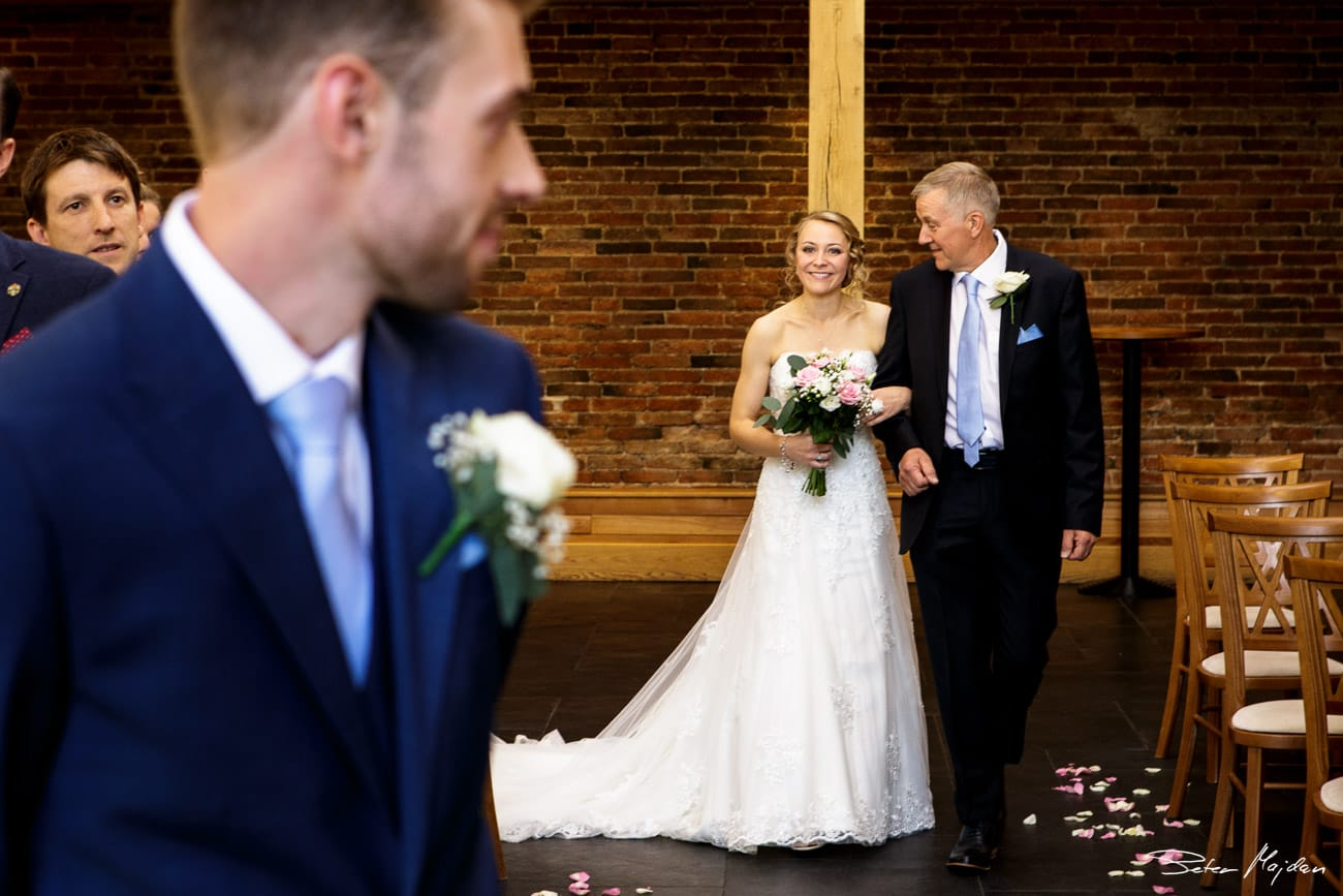 bride arriving for ceremony in oak barn