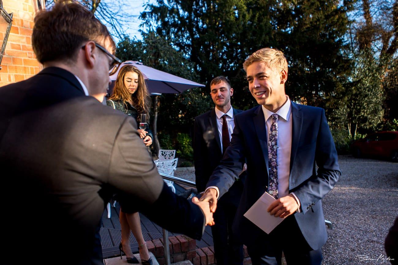 wedding guests greeting groom