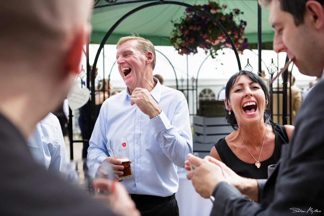 wedding guests laughing at walled garden