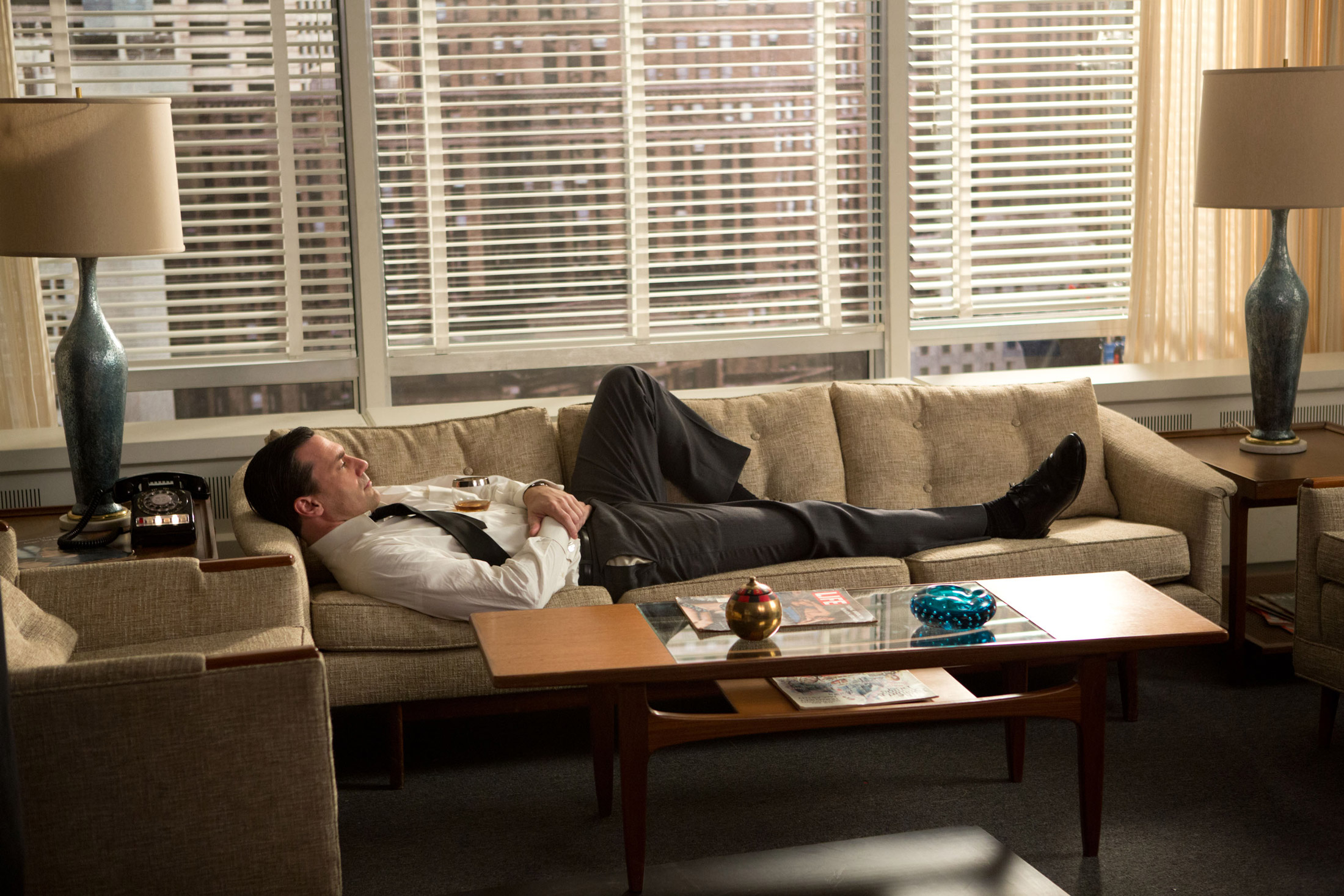 Don Draper's office featuring a mid-century modern sofa between a pair of blue glazed ceramic lamps and G-Plan teak coffee table designed by V.B Wilkins (Season 6).