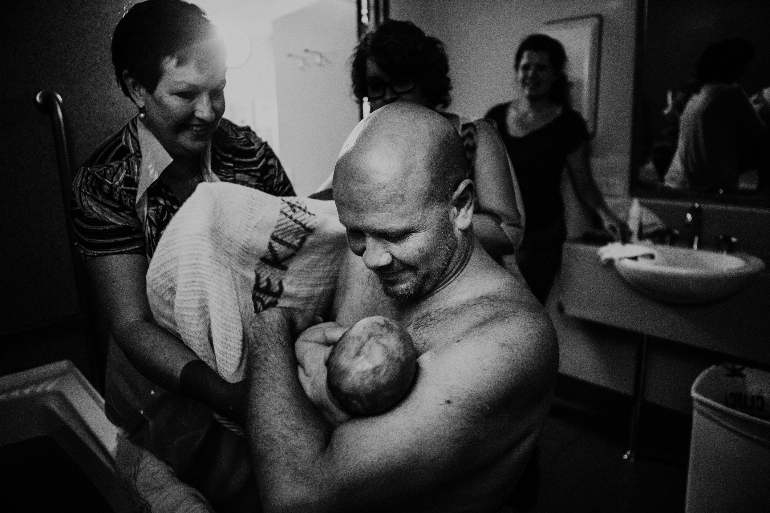 newborn-Skin-to-skin-with-father-hospital-birth-photography-midwife-passing-baby-wollongong-mgp-midwifery-group-practice