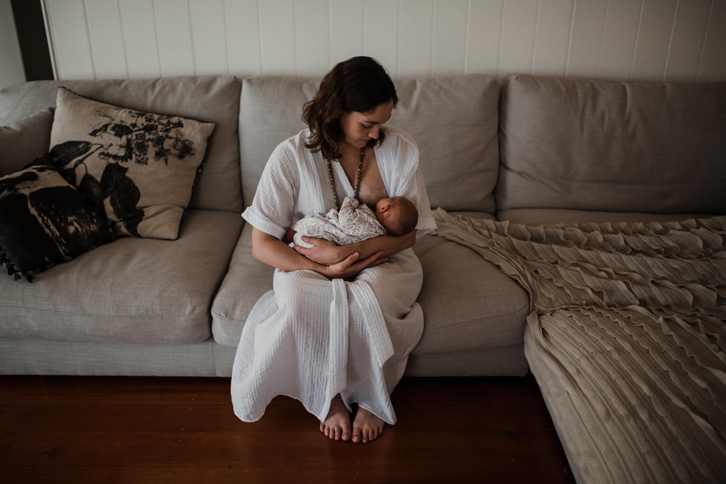 mum breastfeeds newborn baby on couch Townsville