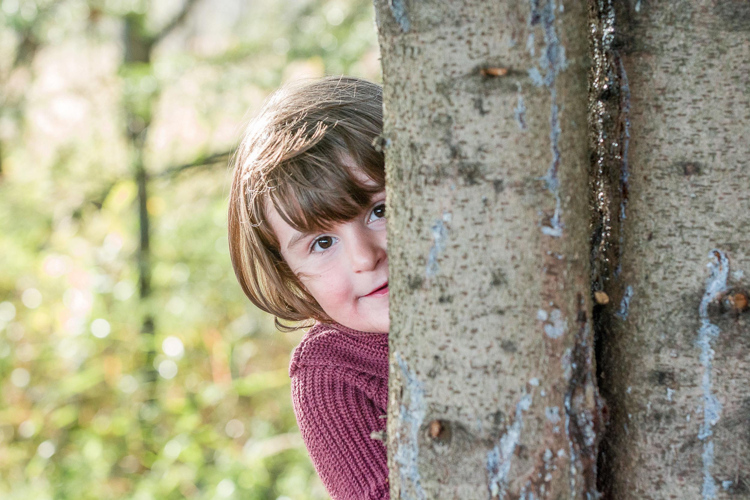 girl peering around a tree