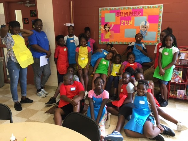 "Coach Allison Srinivasa and students from Thomas ""Jet"" Jackson recreation center in St. Petersburg, FL pose for a group photo in their colorful aprons, a new addition to our program this year."