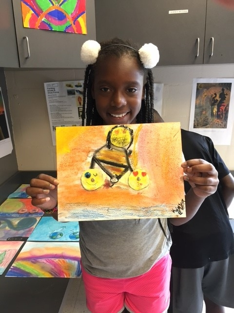 A student from Child's Park recreation center adds a 3D head in addition to wheels to her Franken Bike art piece.