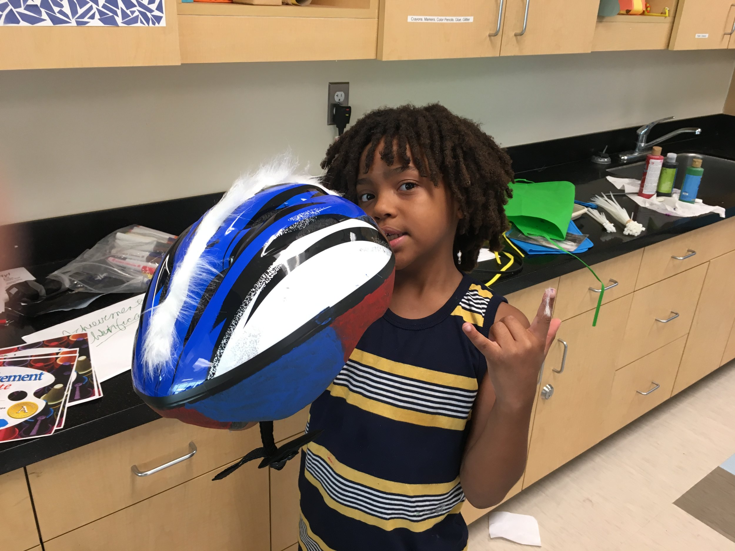 This student at Campbell Park chose white fun fur to accent a blue and white helmet. Fun Fur was attached with plastic zip ties or ribbon. Bicycle Helmets were  sized during the student's introductory visit to the Dalí Museum. Helmets were then ordered. Before Helmets could be decorated, the fit required individual adjustment to chin straps and rear tension screws. During class each student was custom fit to the helmet that was their correct size and color choice.  Then the fun really began!