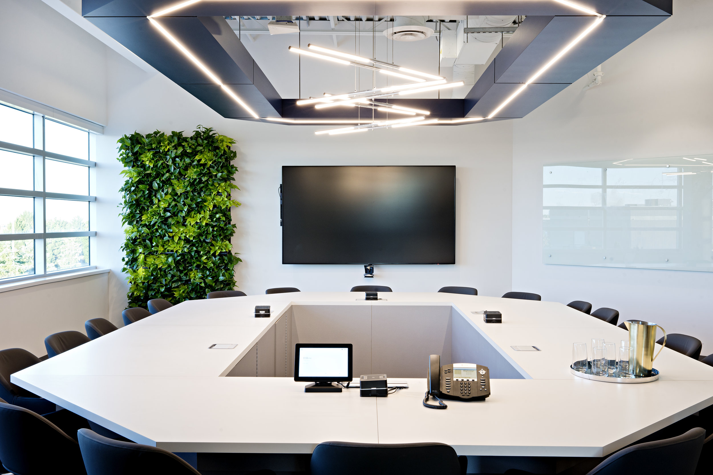 pizzale design interior design commercial office space green living wall white painted walls natural light large windows custom angled desk large wall mount tv modern contemporary light fixtures glass white board.jpg
