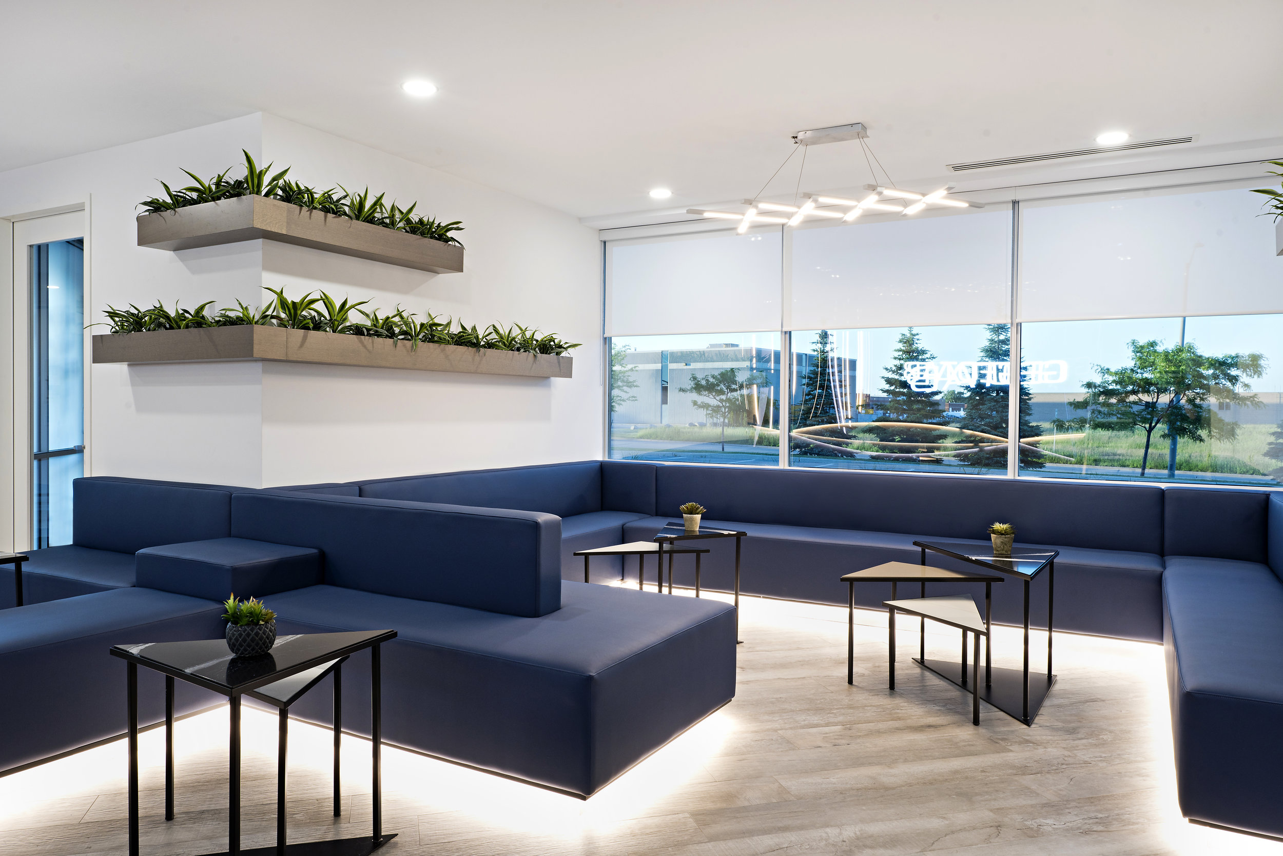 4pizzale design intrerior design commercial office space reception banquette seating navy blue vinyl led lighting stained white oak self watering planter white roller blind grey laminate floor custom metal and stone nesting table modern light fixture.jpg