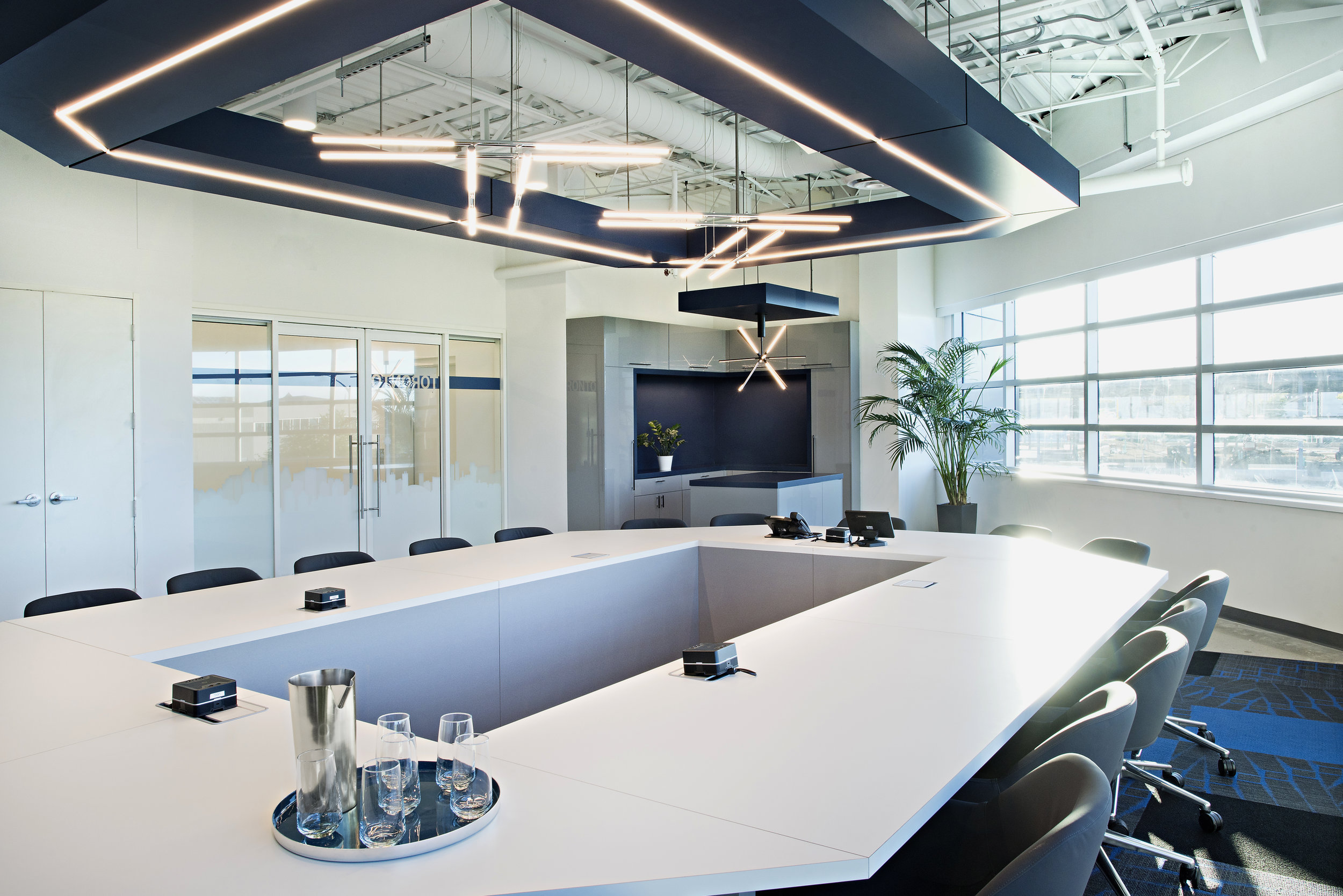 10 pizzale design interior design commercial office space conference room modern contemporary light fixture grey and blue small kitchen space custom desk power modules natural light glass sliding doors black hardware indoor palm tree black planter.jpg