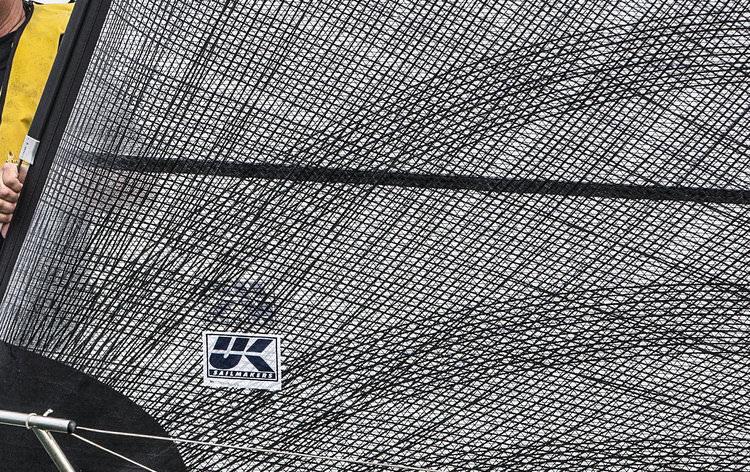 Närbild på X-Drive tejper nära genuans halshorn. Den mörka horisontella linjen är en vådsöm. X-Drive tejperna är laminerade över sömmarna vilket förhindrar att sömmarna överbelastas och försämrar seglets form.