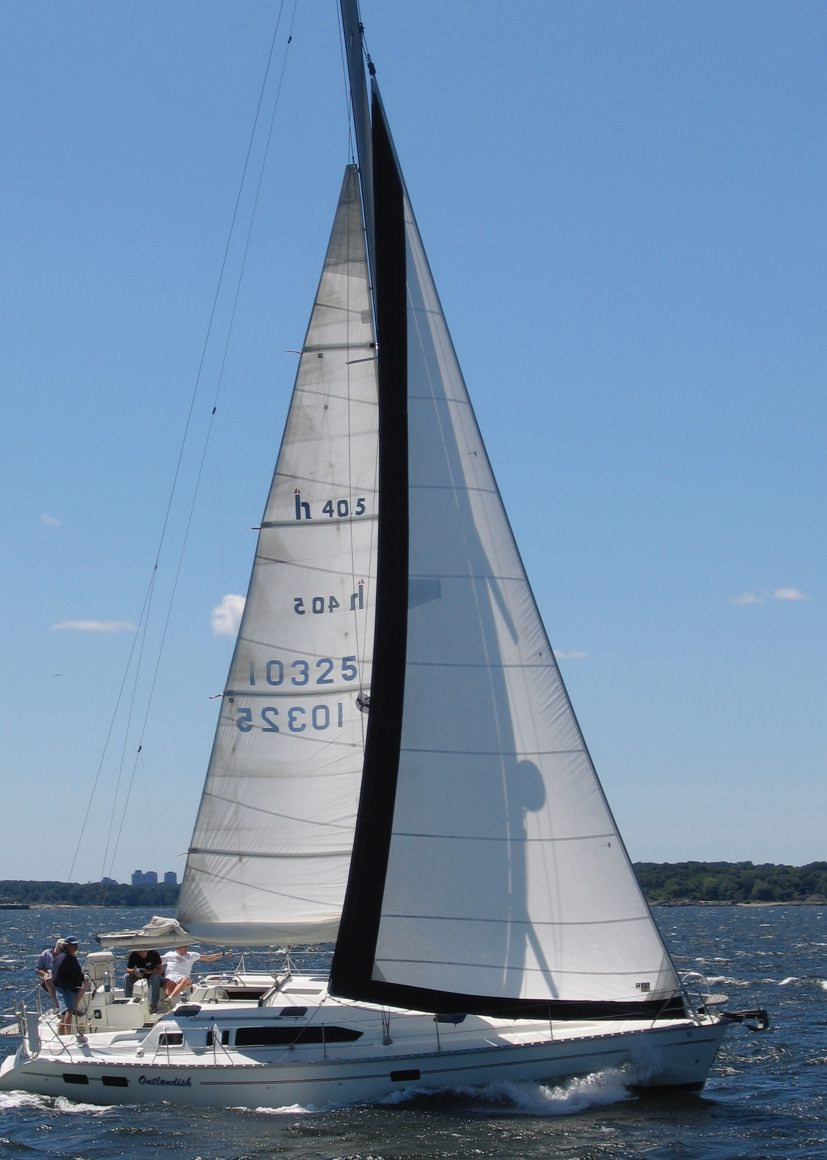 Above a Hunter 40.5 with a navy blue UV leech and foot covers sewn to the sail. Below: The same sail roller furled showing the UV covers protecting the sail.