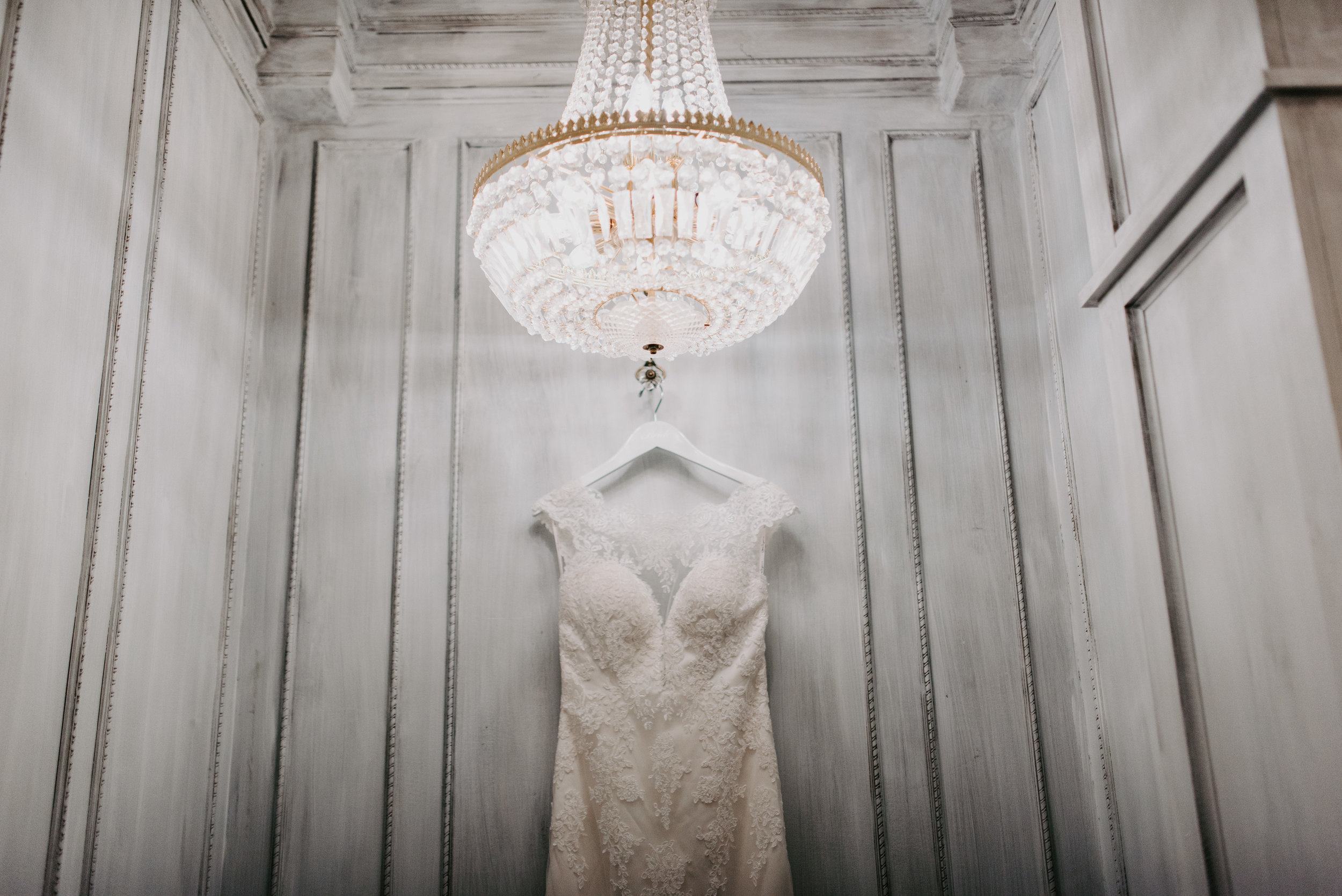 lace wedding dress under chandelier with white walls