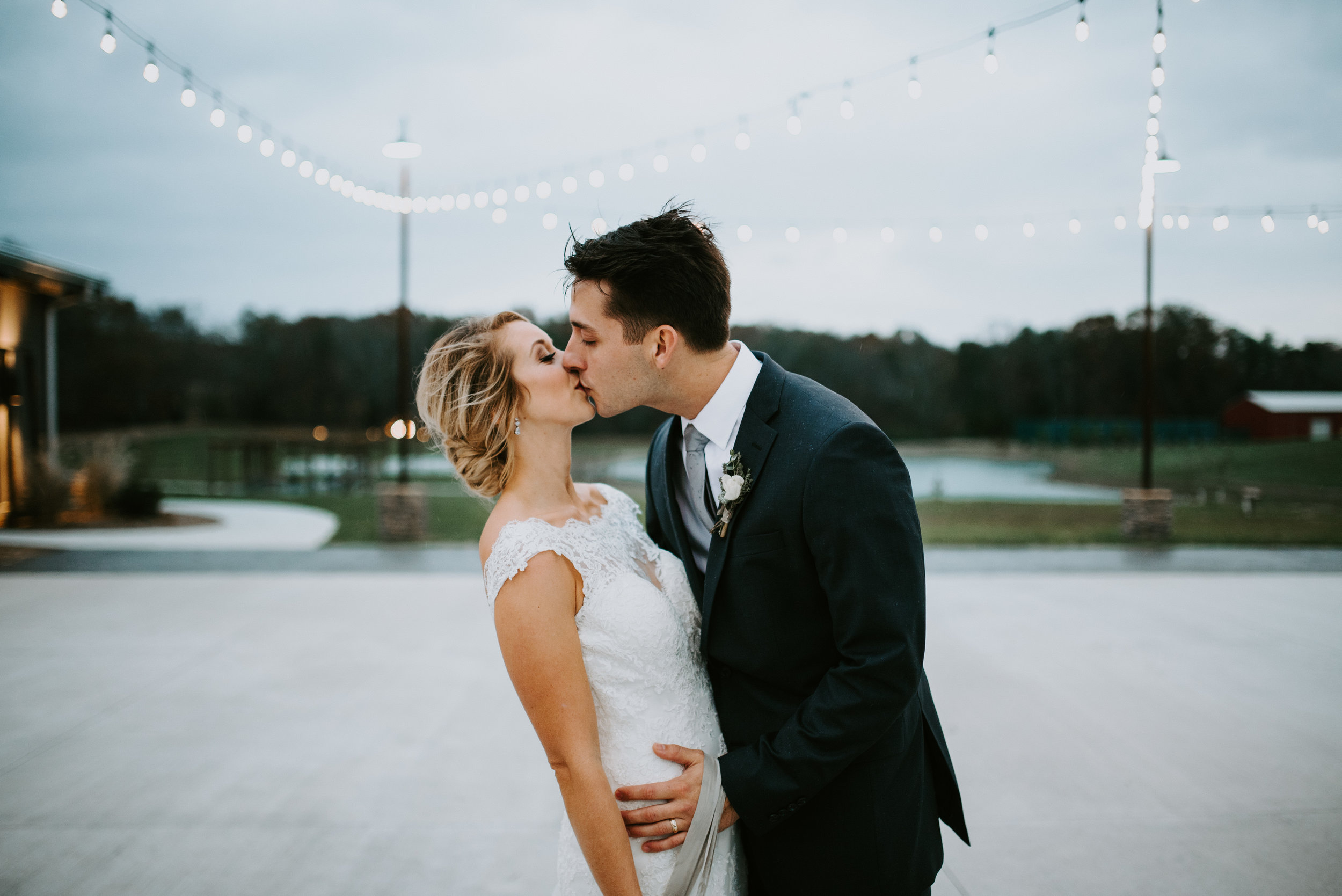 kissing in the rain under twinkle lights wedding picture bride and groom
