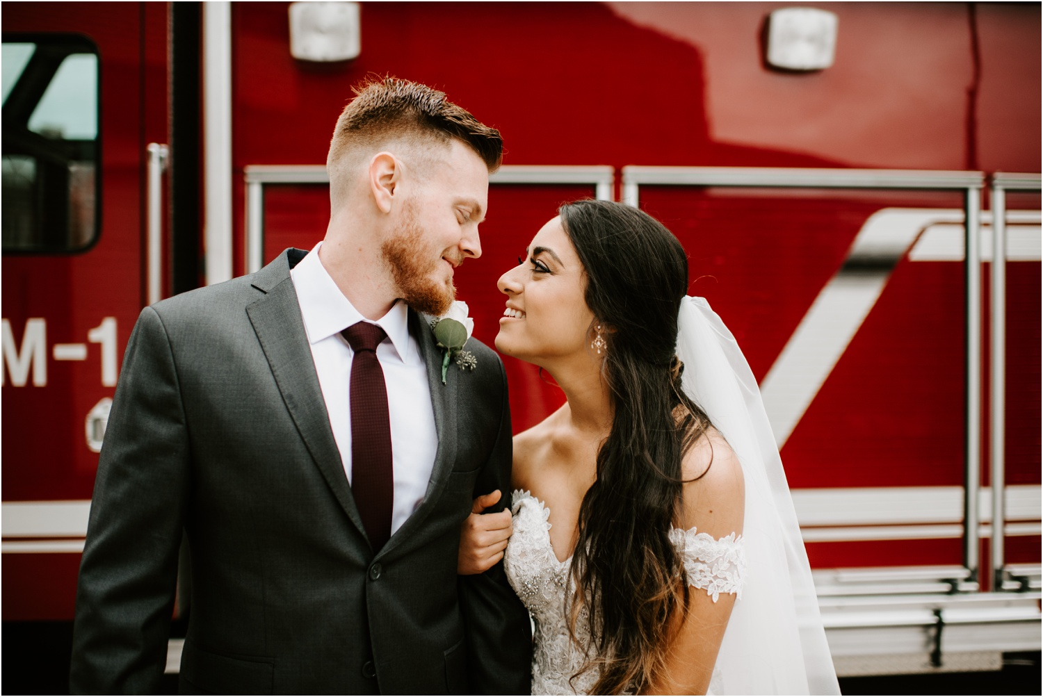 bride and groom in front of red fire truck