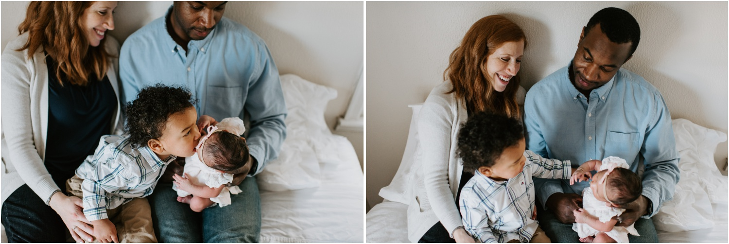 toddler kissing newborn baby family sitting on bed