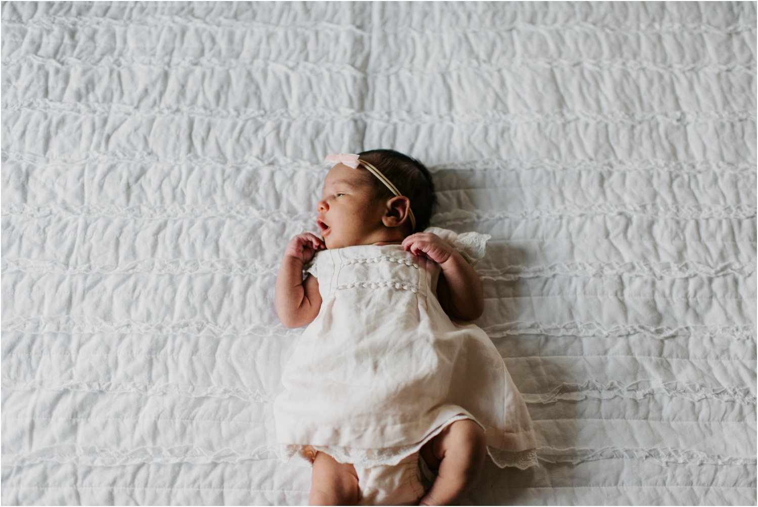 newborn laying on white bed with pink bow