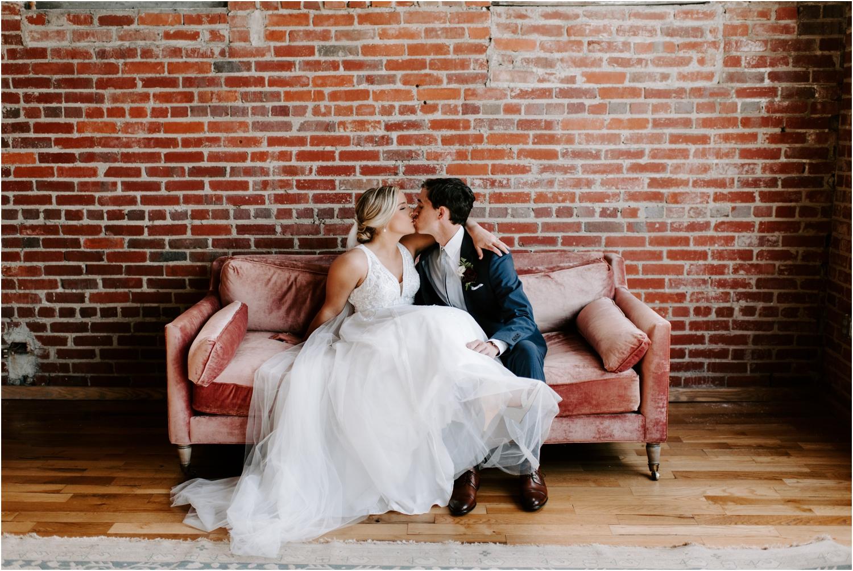bride and groom kissing on velvet couch