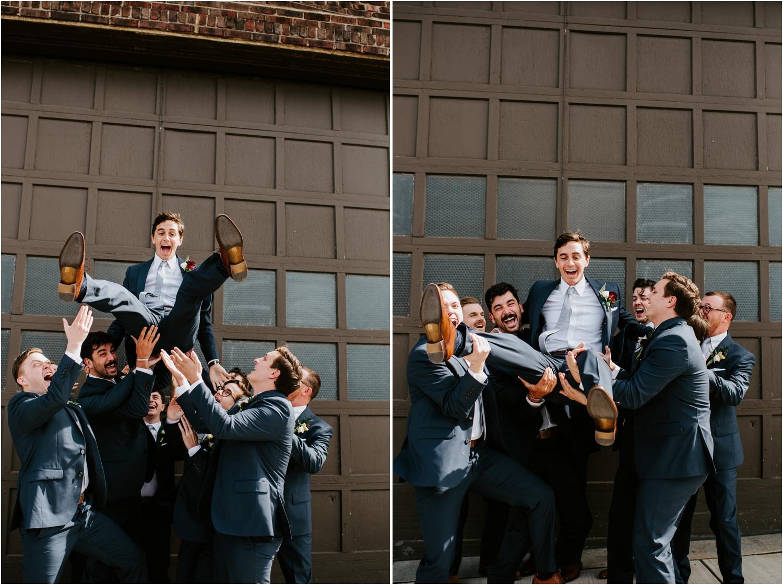 groomsmen in navy suits throwing groom into the air