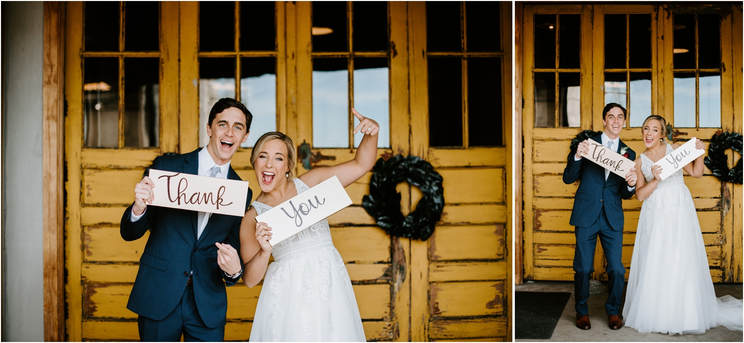 bride and groom with thank you signs
