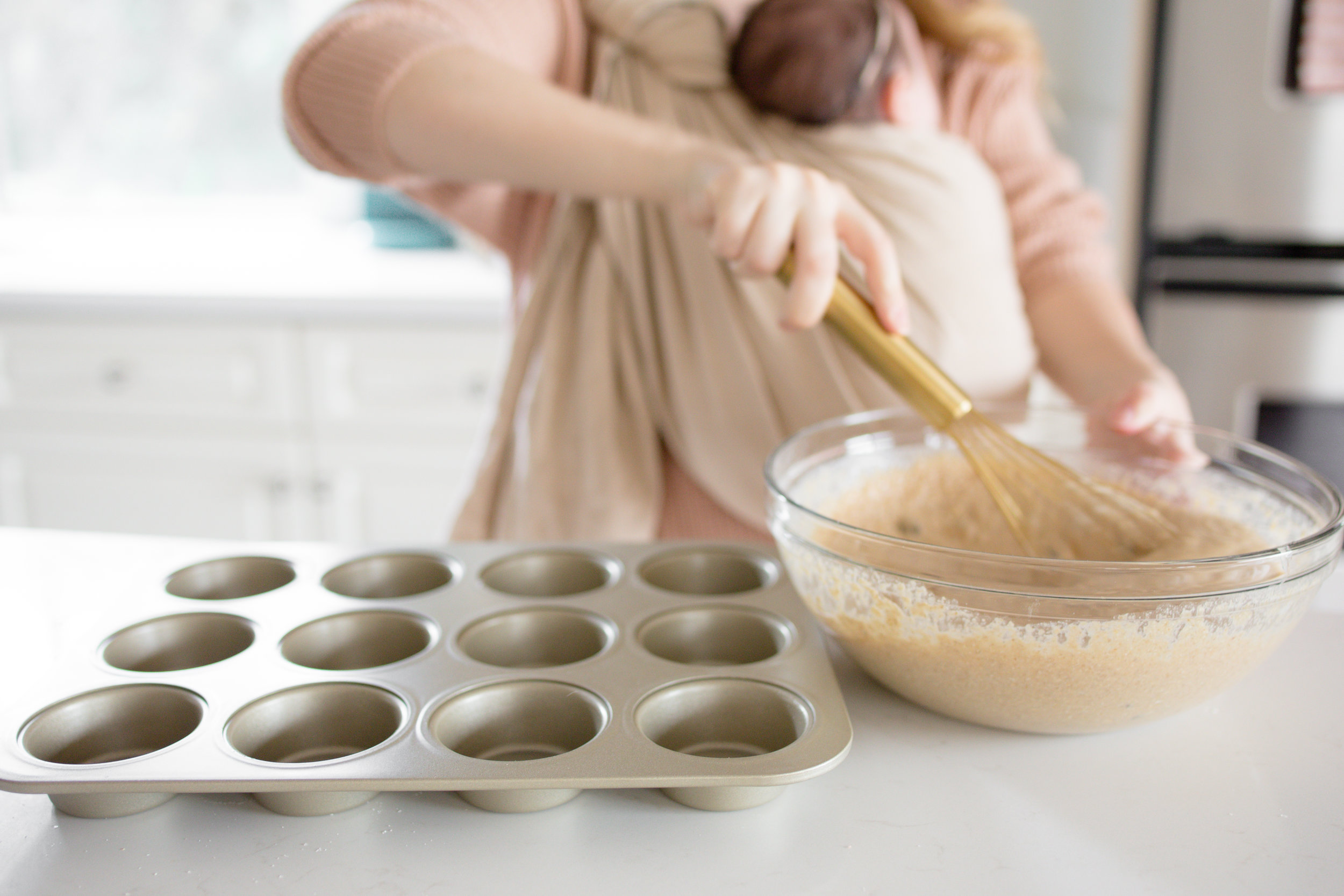 Mom wearing ring sling stirring muffin batter