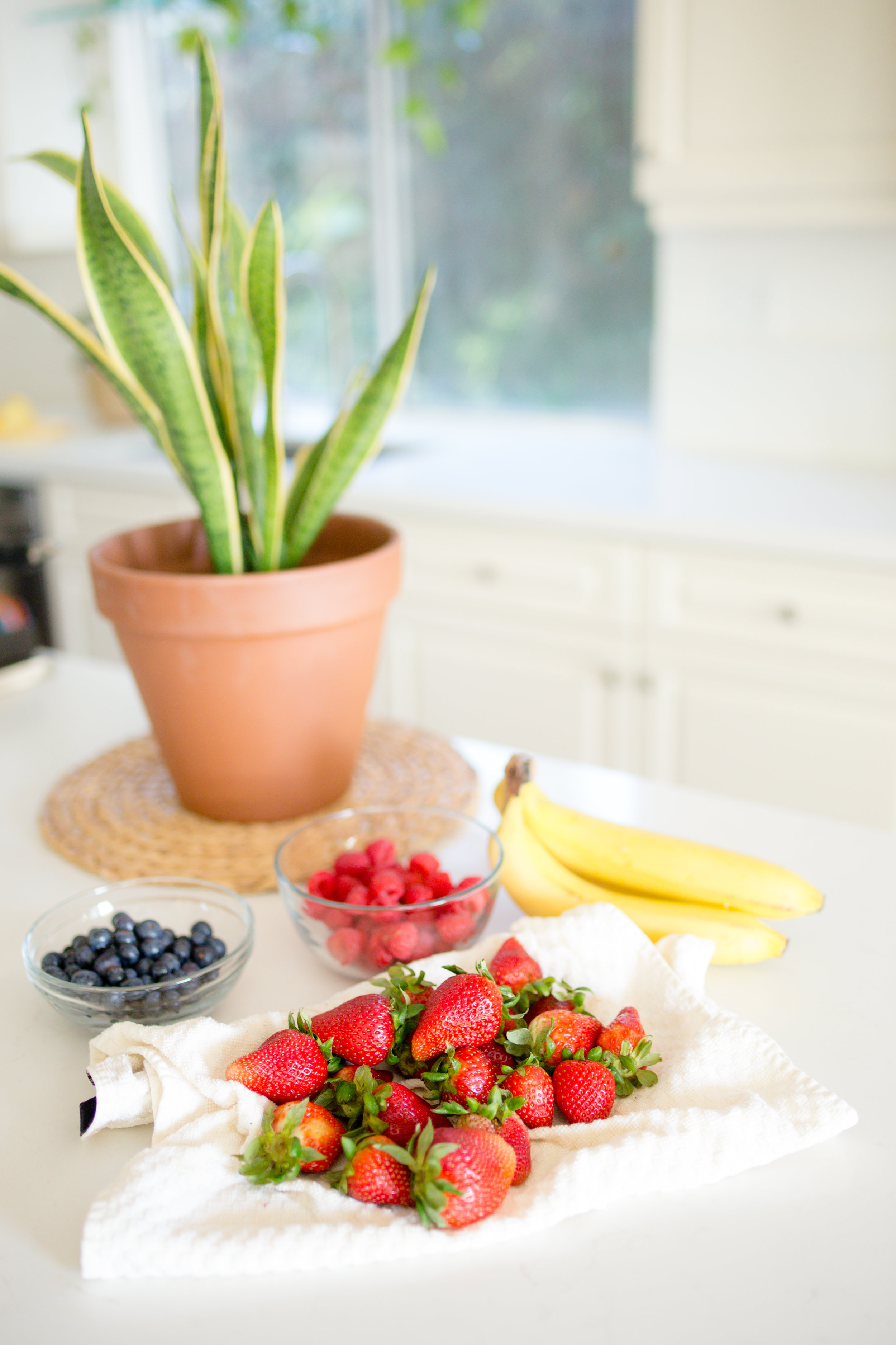 Freshly washed strawberries, blueberries, and raspberries ready to be used in a healthy breakfast banana split
