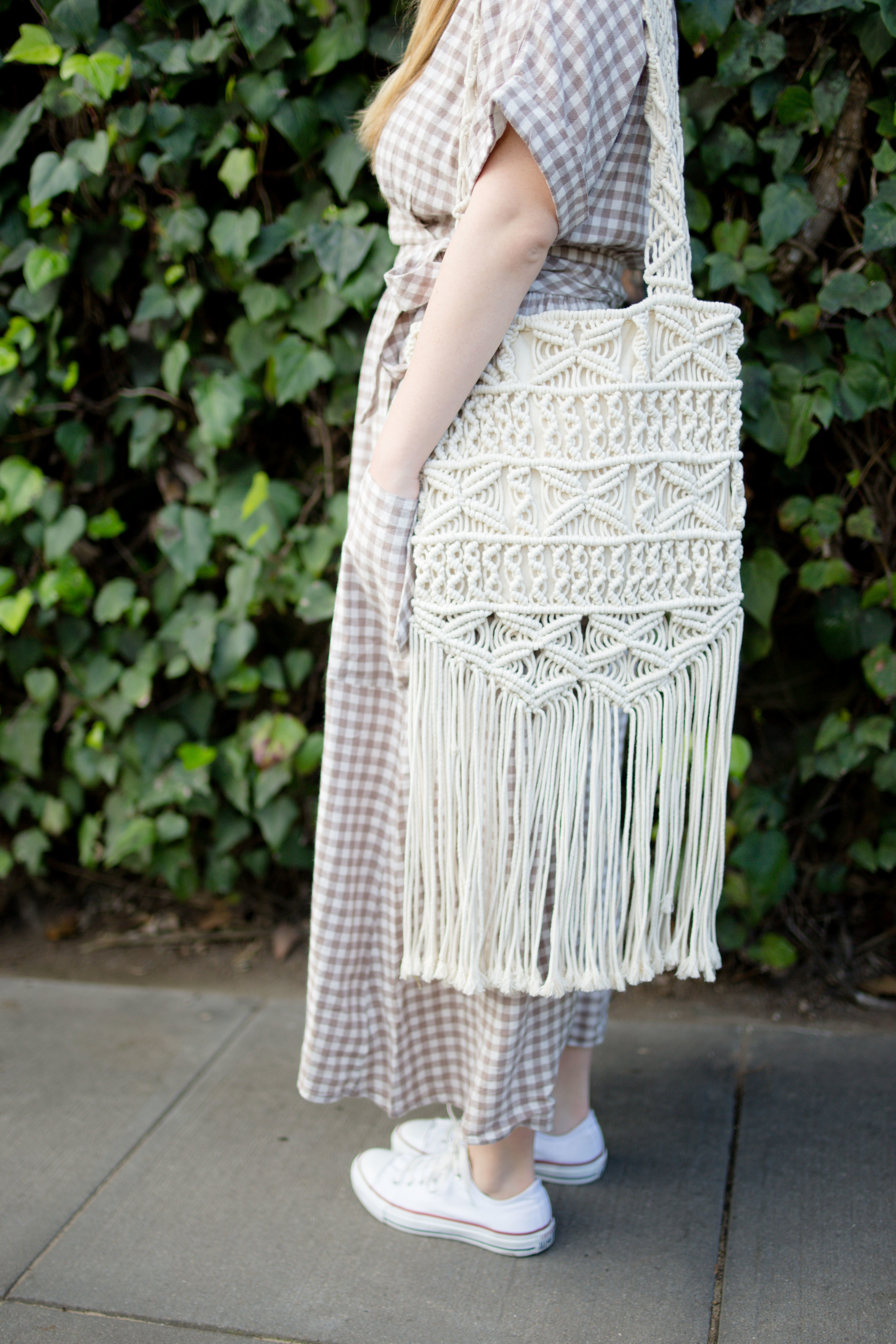 Streetstyle of Girl Wearing UO Gabrielle Linen Midi Wrap Dress and white converse chuck Taylors and macrame purse